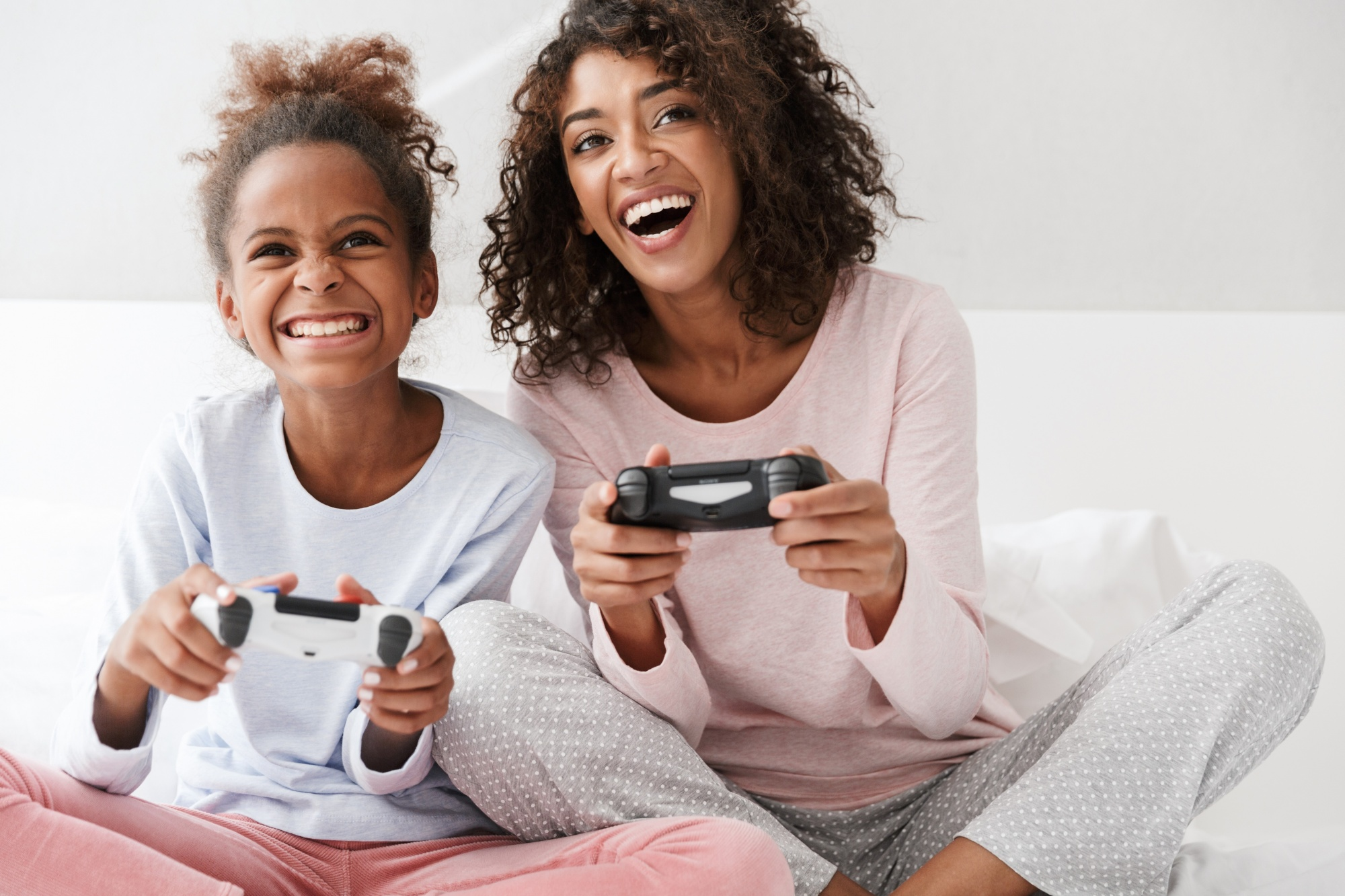 What is neuroplasticity? Black mom and daughter in pjs playing video games