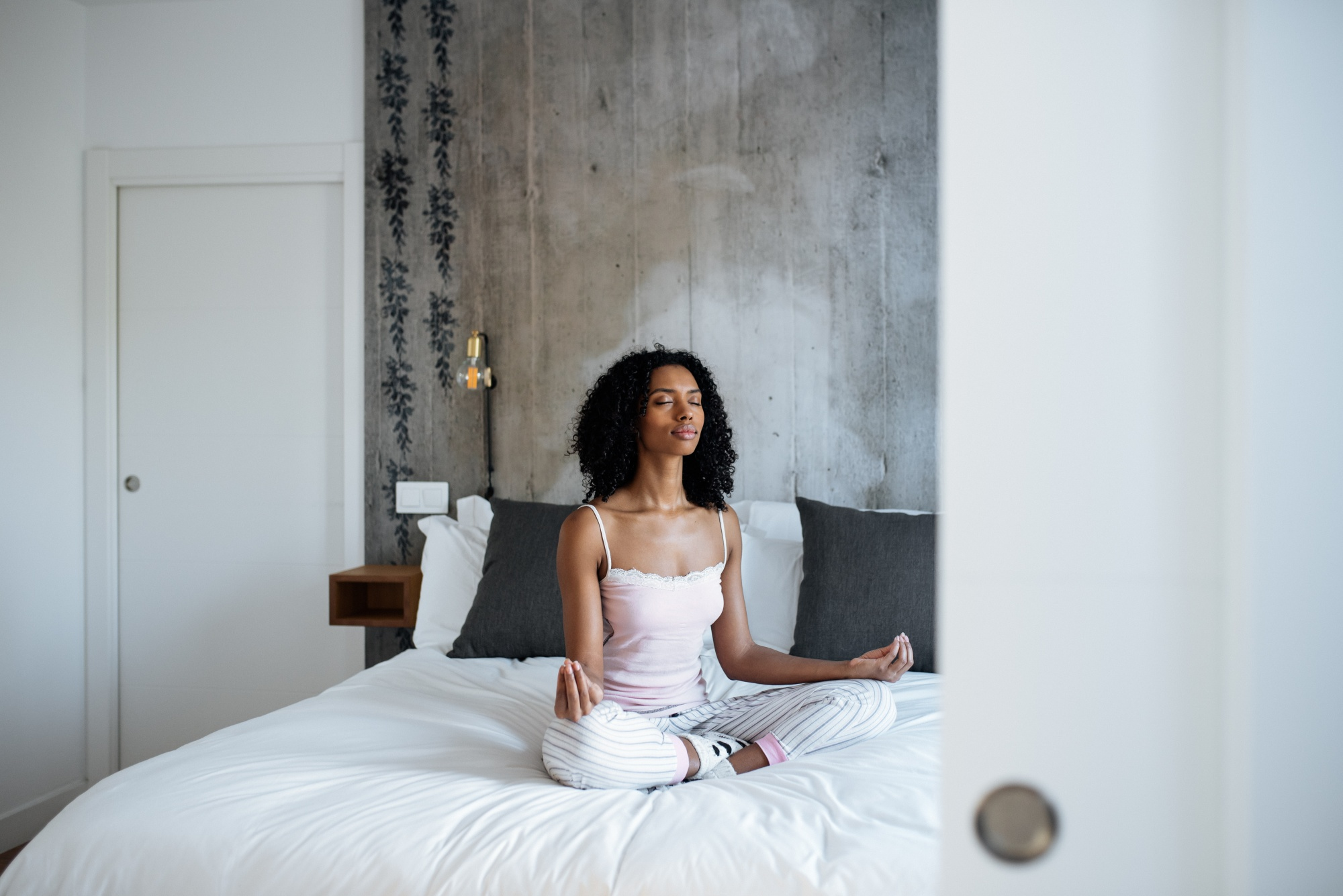 better sex after menopause, Attractive black woman sitting in lotus position on bed meditating