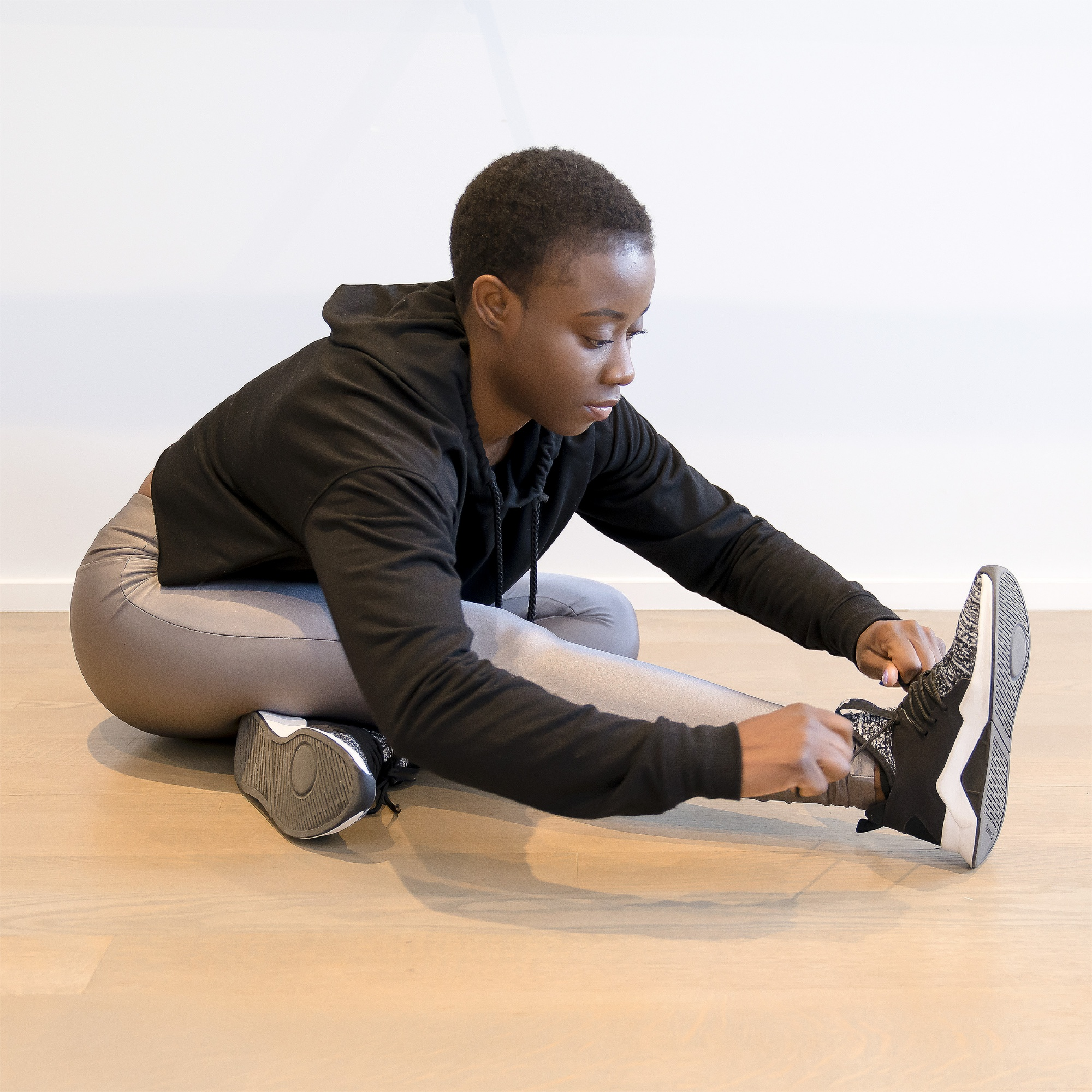 How to Avoid Exercise Injury Over 40, Black woman with pixi and silver leggings black crop hamstring stretch