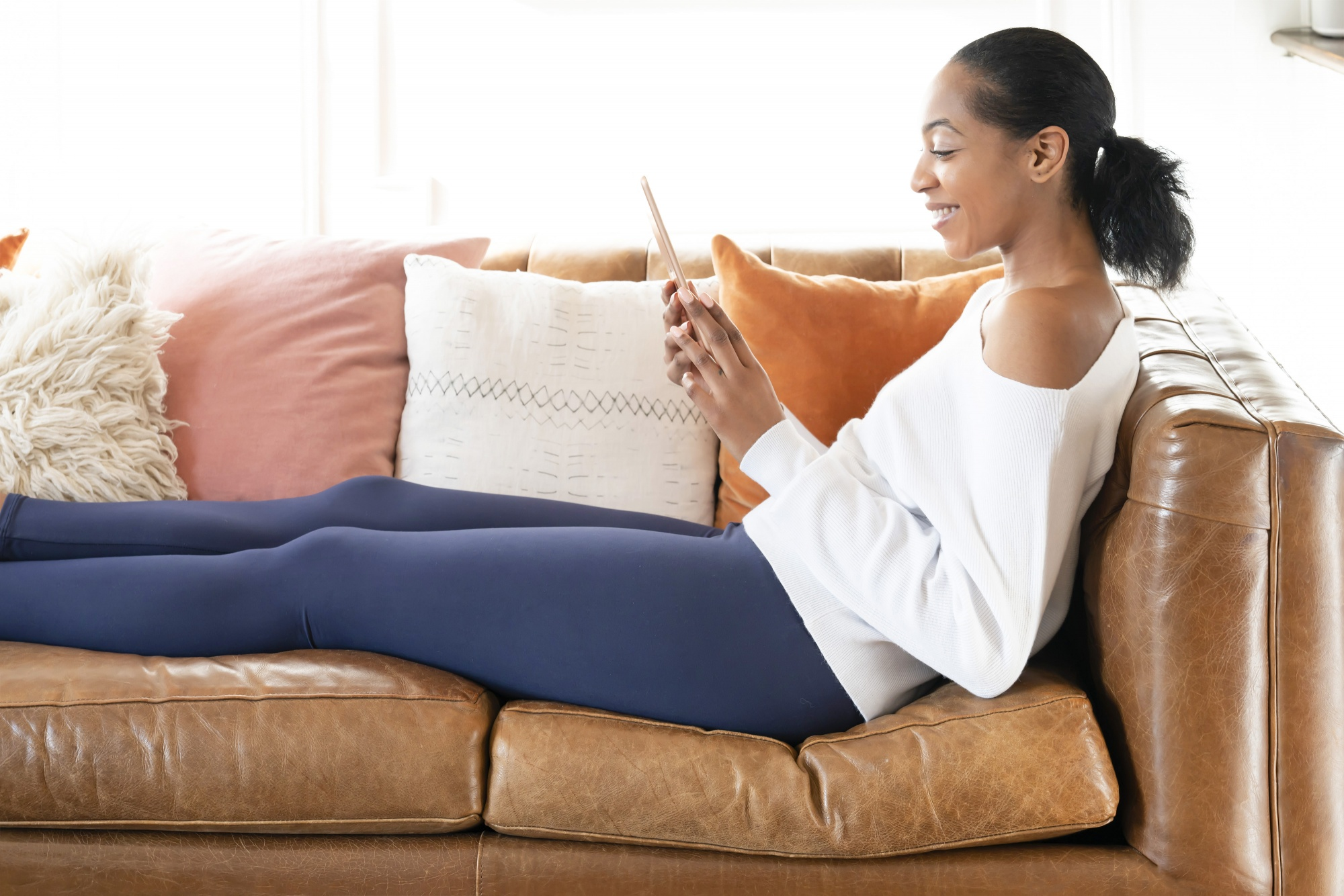 How to Avoid Exercise Injury Over 40, Black woman with ponytail blue leggings white shirt on leather couch reading tablet