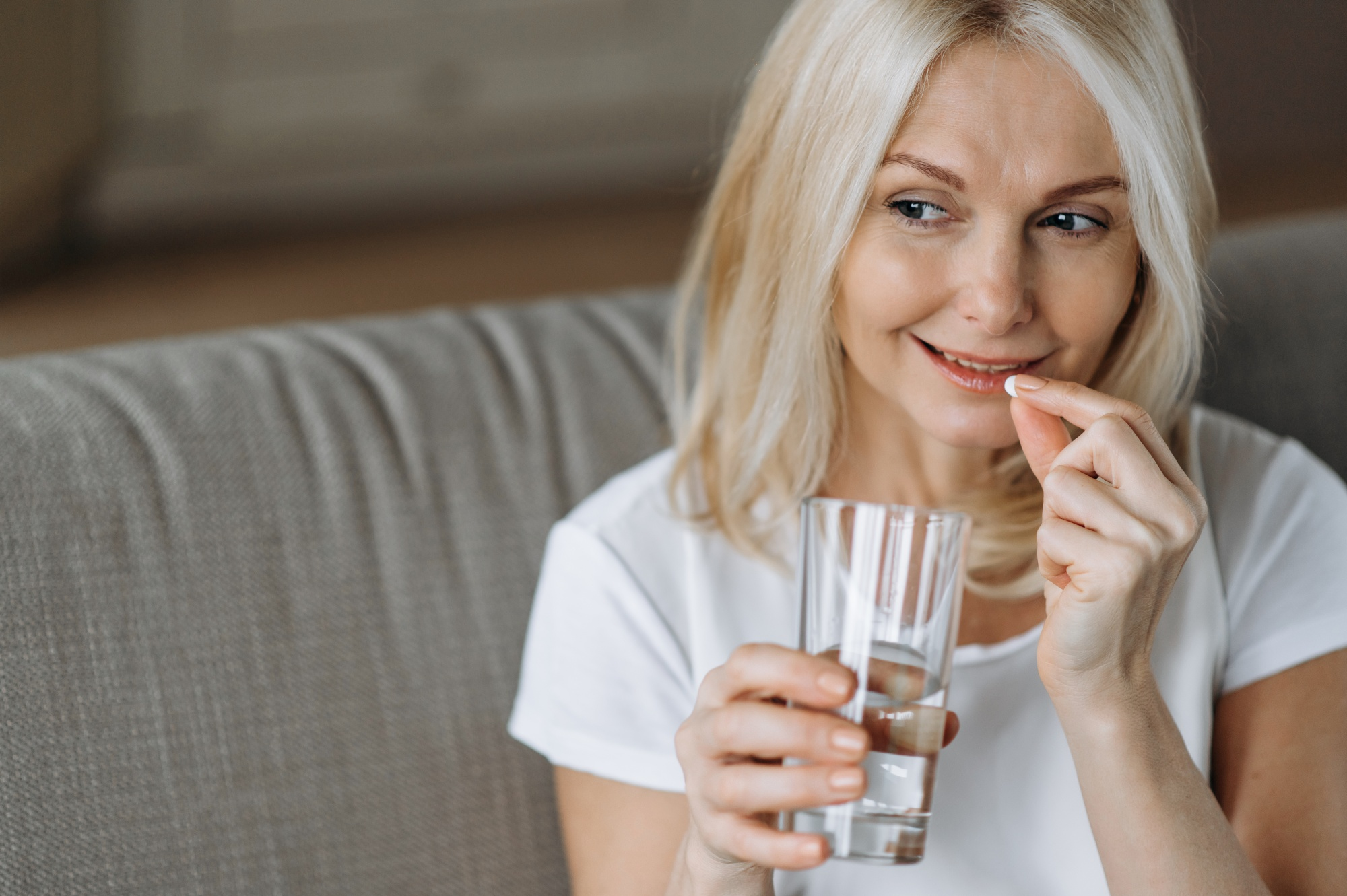 get rid of mummy tummy for good, Blonde bobbed woman on couch taking supplement