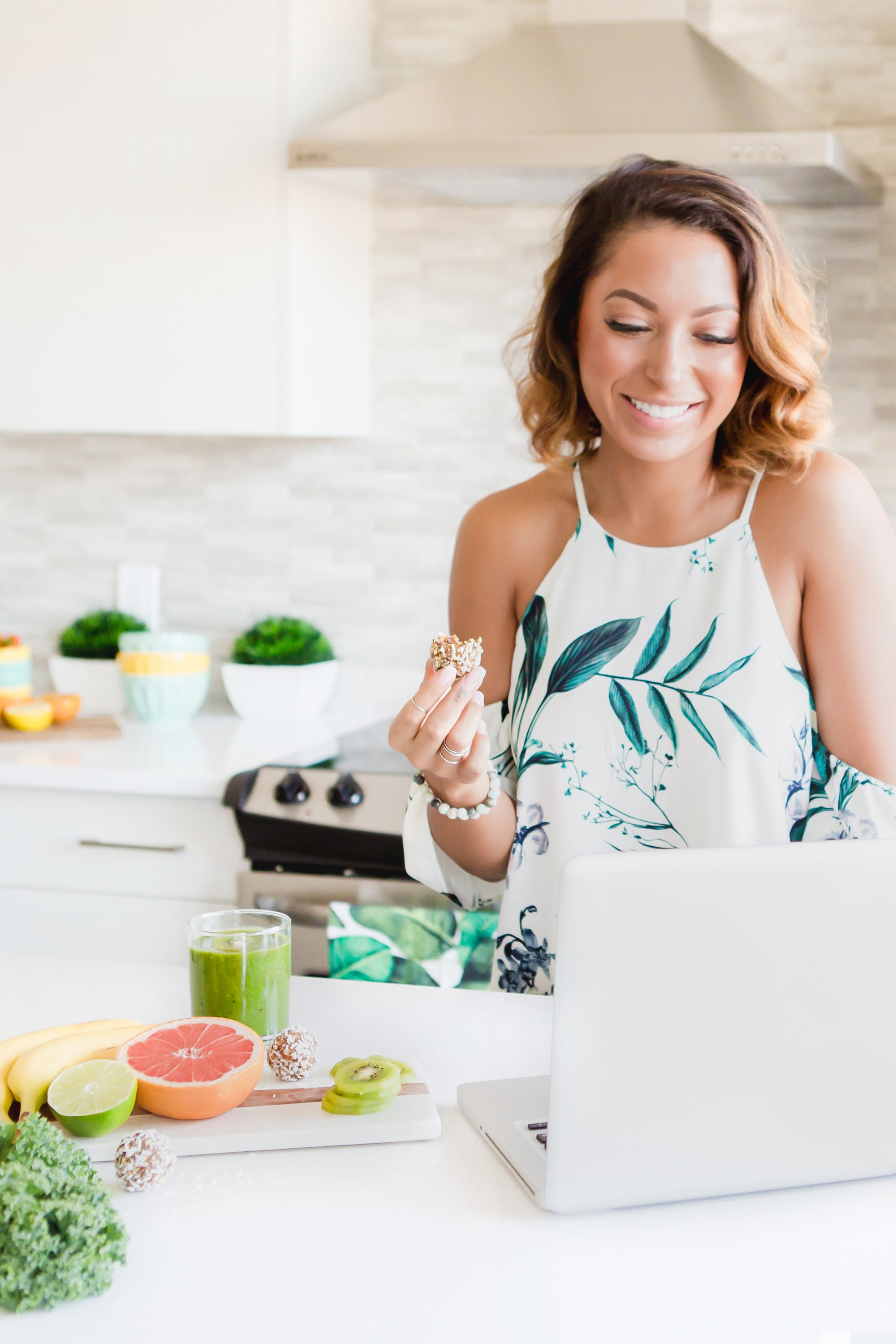 intermittent fasting and intuitive fasting, Bobbed woman with green smoothie at computer in white kitchen