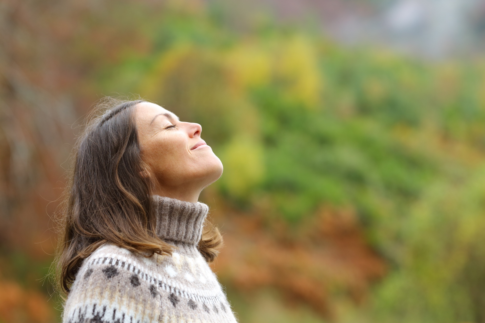 what is neuroplasticity? How to build your brain, Brunette woman in fair isle sweater in autumn face in sun meditating