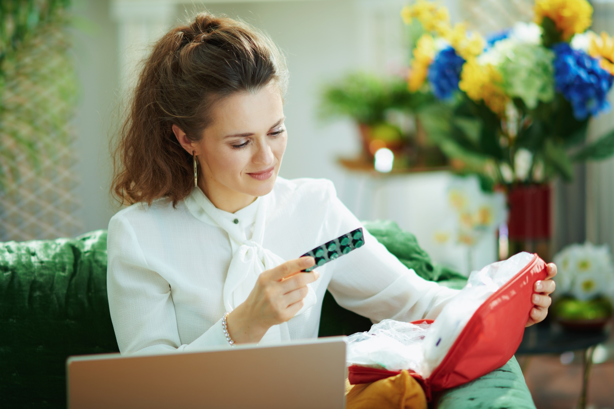 better sex after menopause, Brunette woman in white blouse checking medication at laptop
