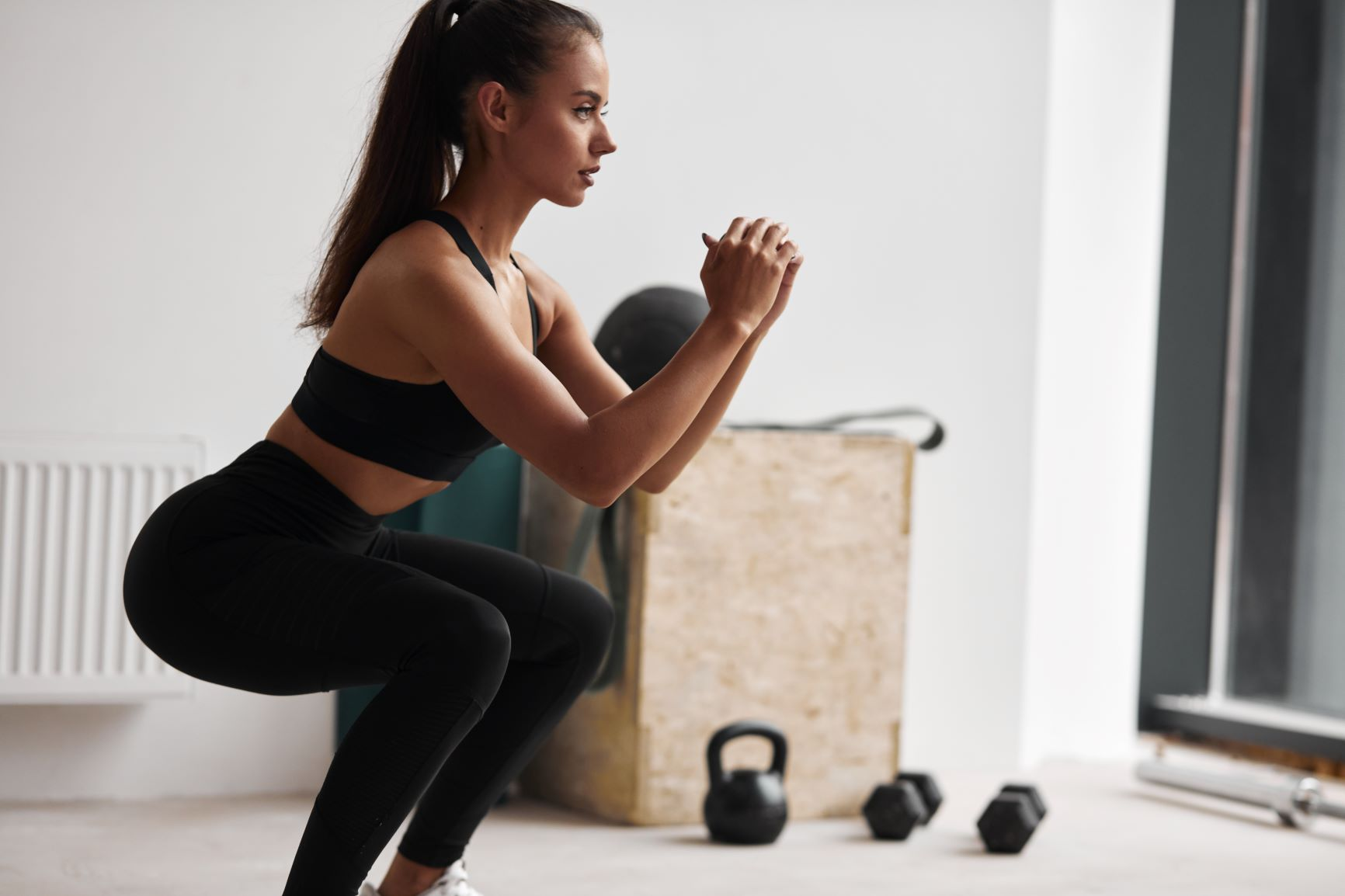 How to Avoid Exercise Injury Over 40, Dark haired woman in black in squat