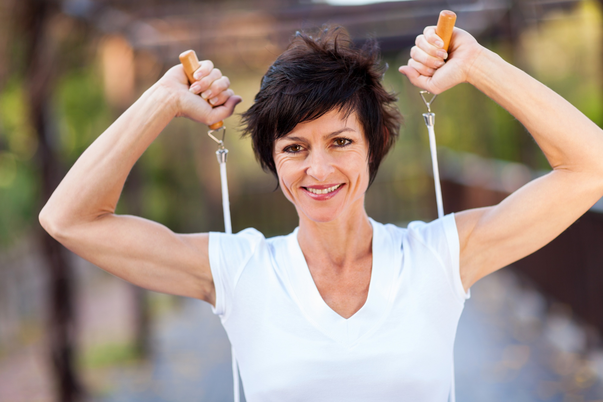 get rid of mummy tummy for good, Dark pixi-haired middle aged woman strong arms with jumping rope