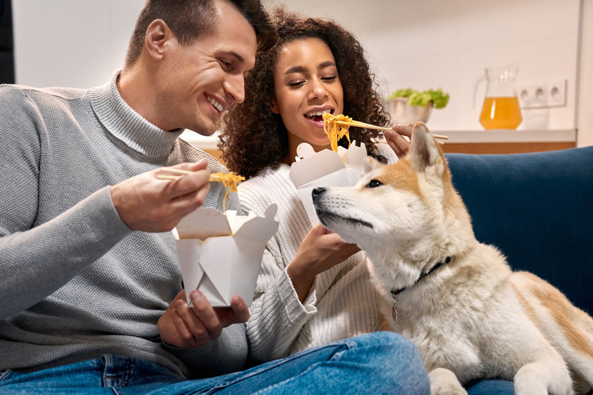 dogs save empty nesters, attractive ethnic couple over 40 sitting on the sofa eating Chinese take-out with their dog