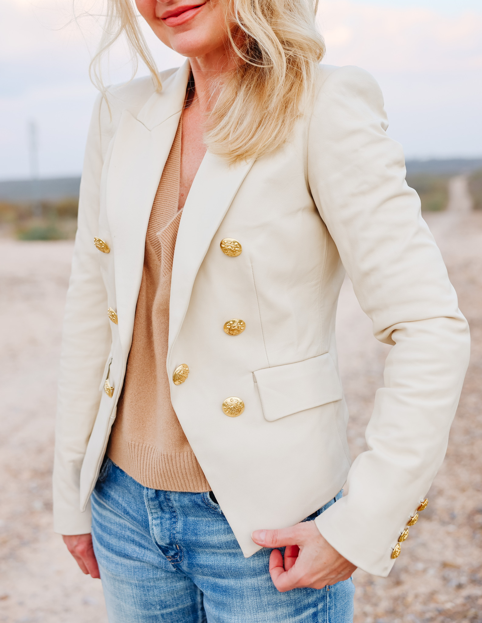 Blazers on women over 40 featuring style over 40 influencer Erin Busbee wearing Veronica Beard cooke blazer in white with camel sweater and moussy jeans
