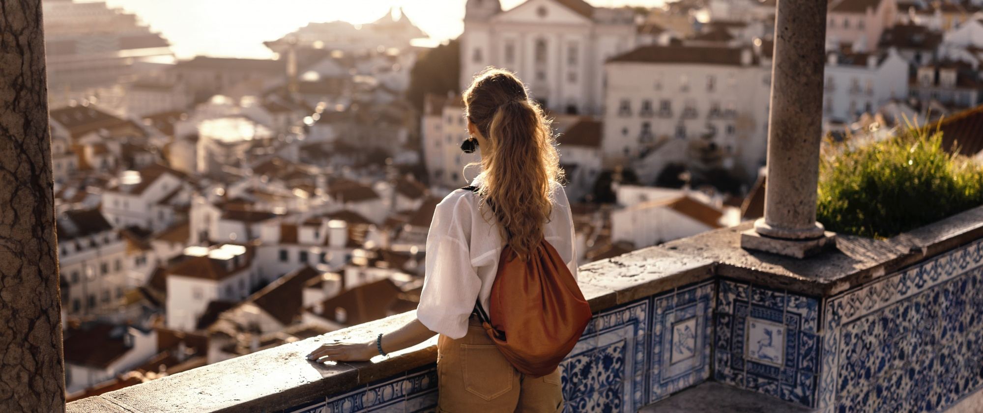what is neuroplasticity? How to build your brain, Long haired ponytailed woman with leather backpack on tiled balcony overlooking city