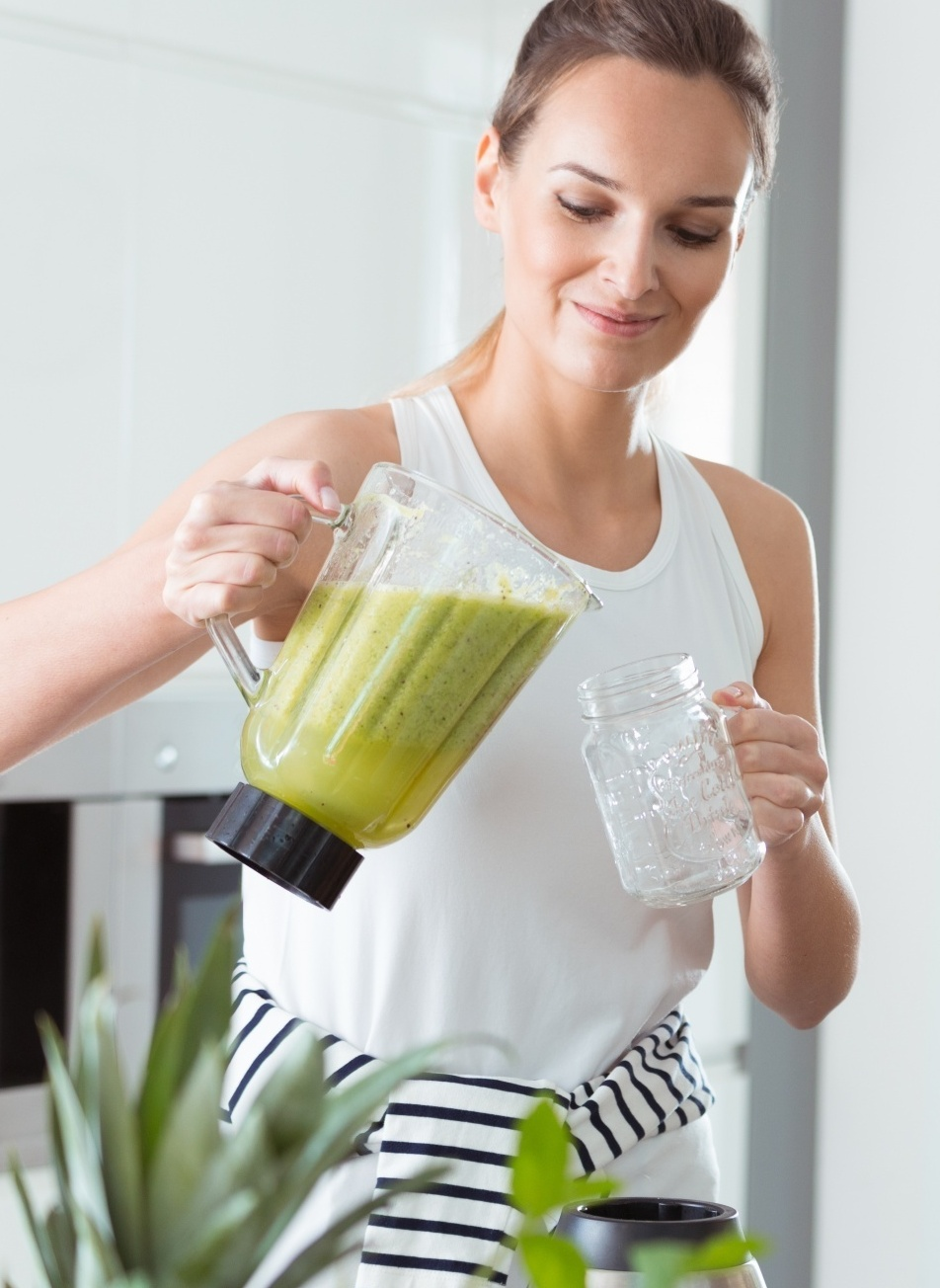 get rid of mummy tummy for good, Pony-tailed woman in white tank pouring green smoothie from blender into ball glass