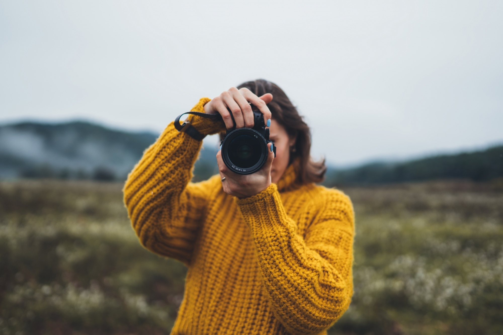 better sex after menopause, Woman in yellow sweater with camera in field with moutain
