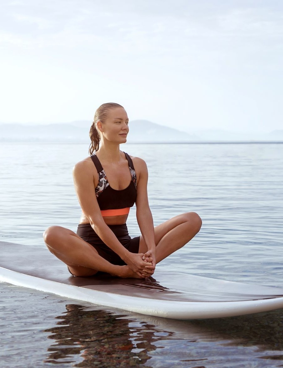 How to Avoid Exercise Injury Over 40 woman in butterfly on paddleboard