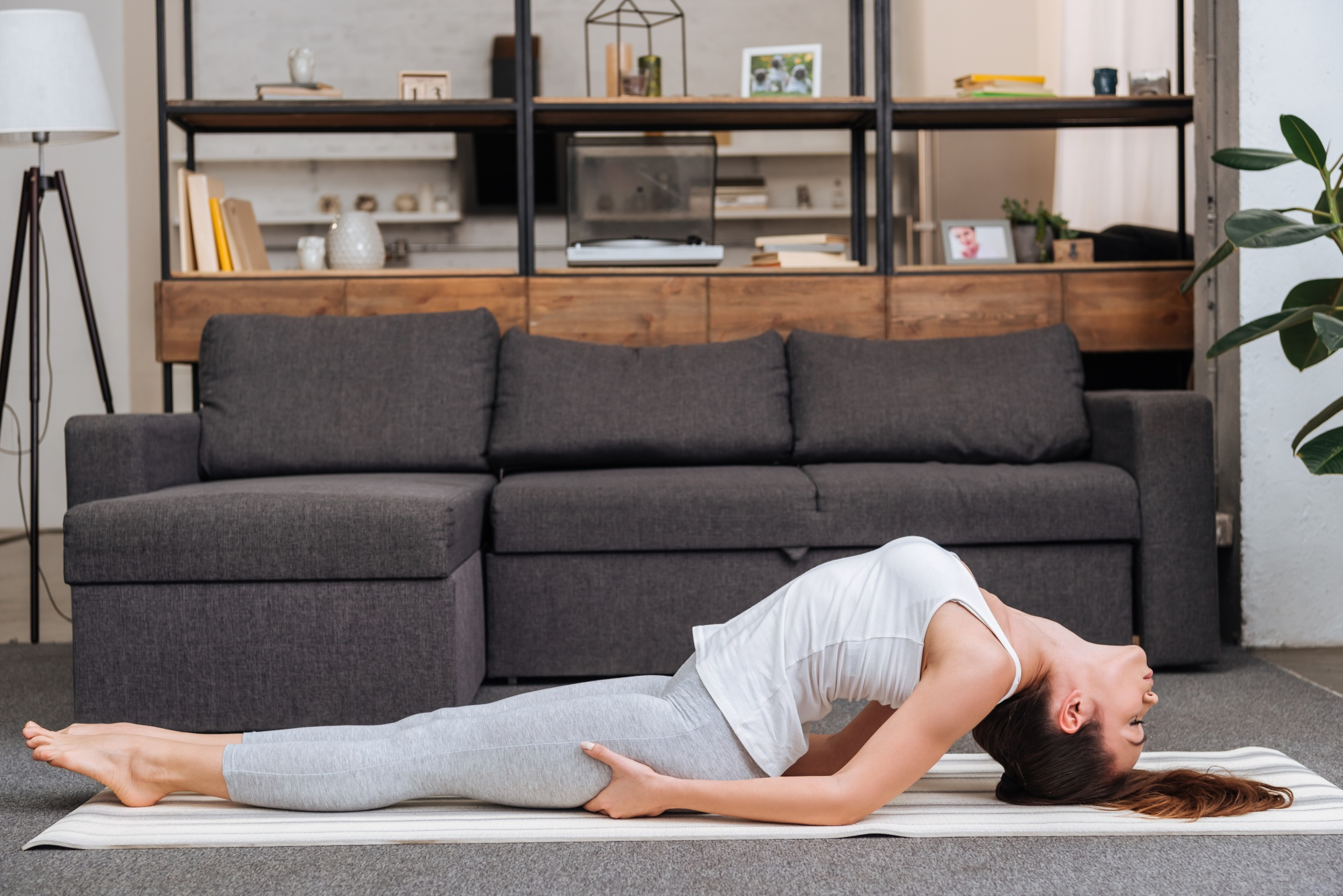 better sex after menopause, woman practicing fish pose at home in living room