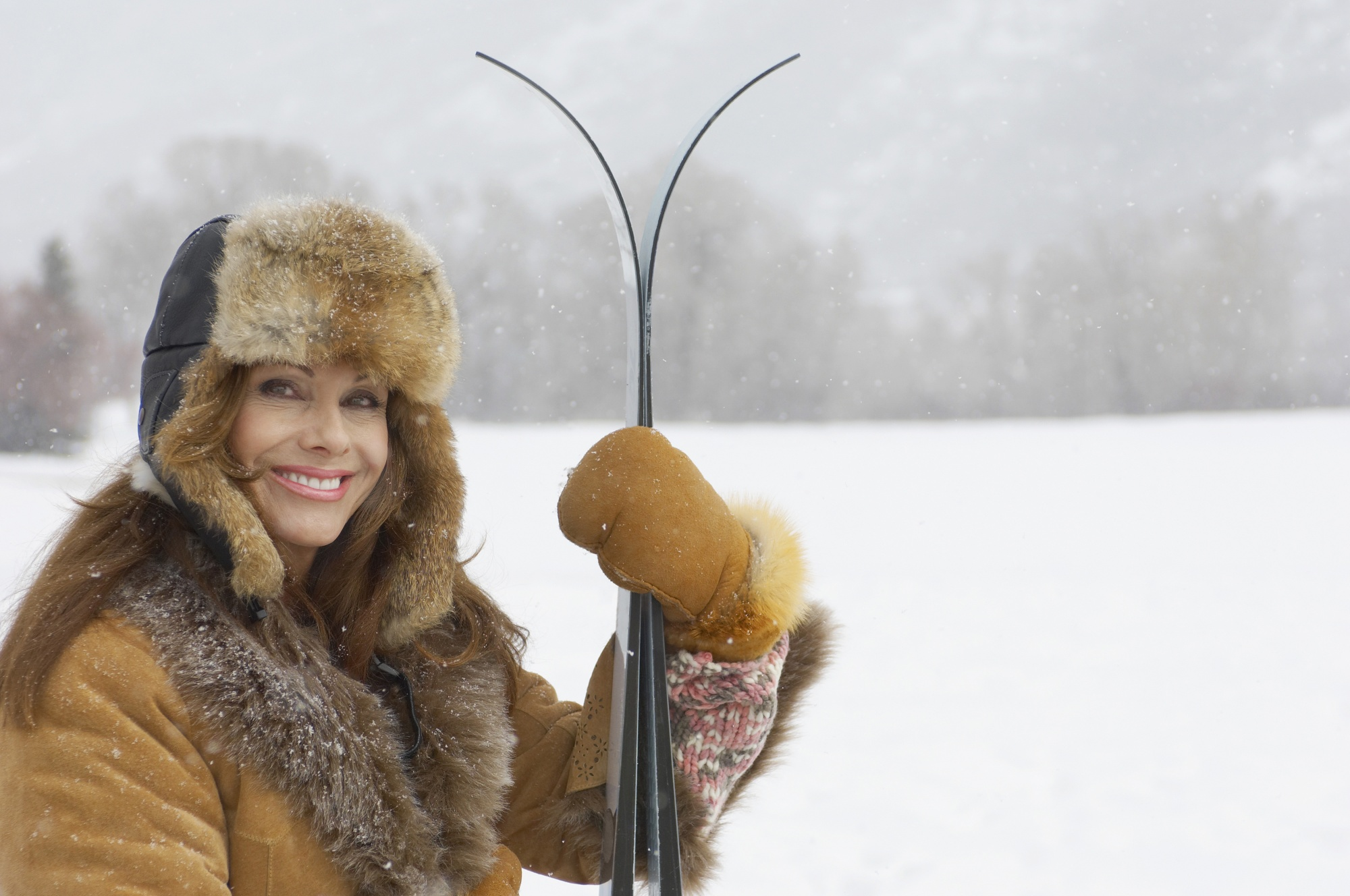 dating profile after 40, attractive woman smiling outdoors in snow with skis