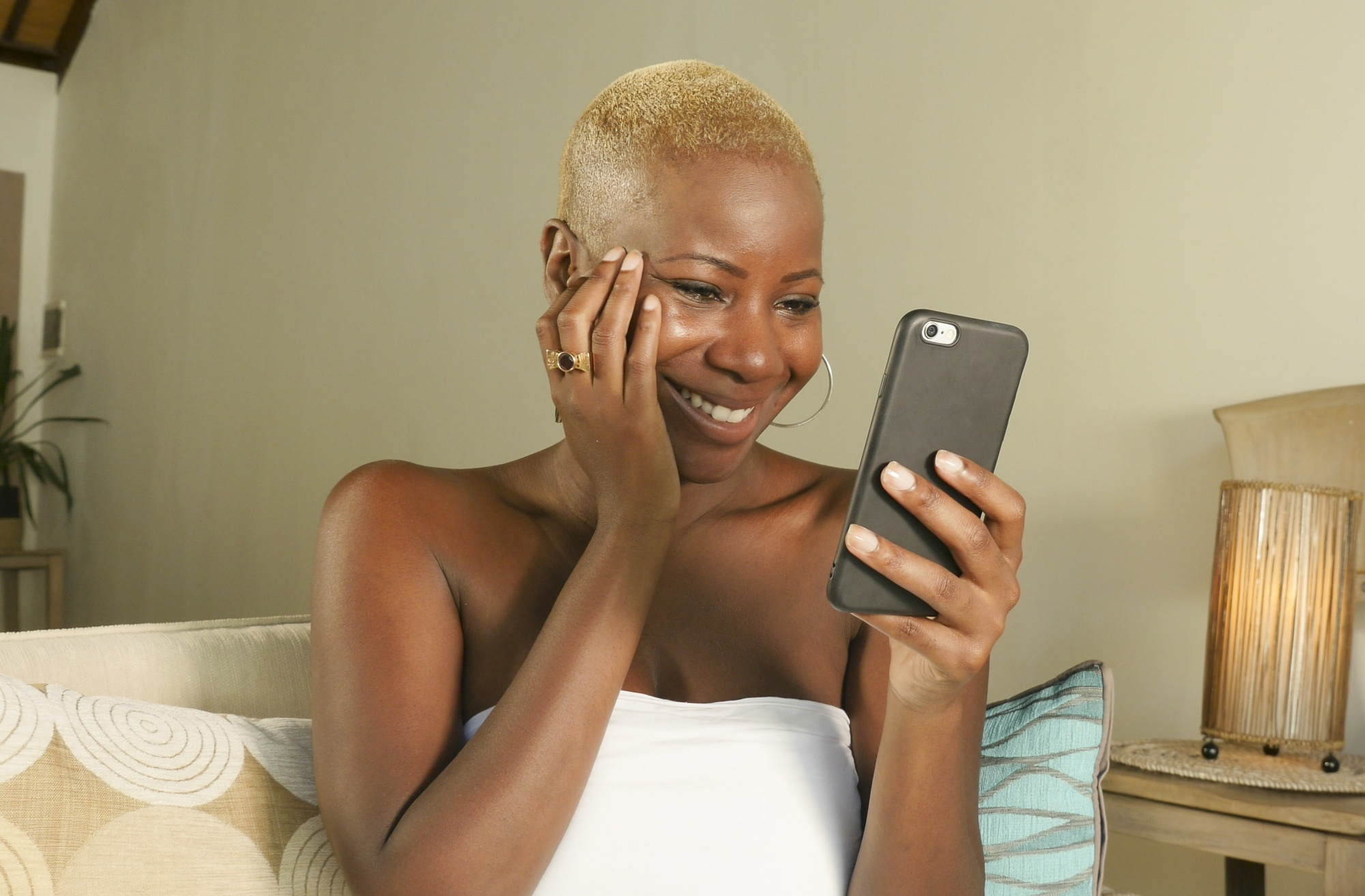 dating profile after 40, African American woman in living room smiling looking at cell phone