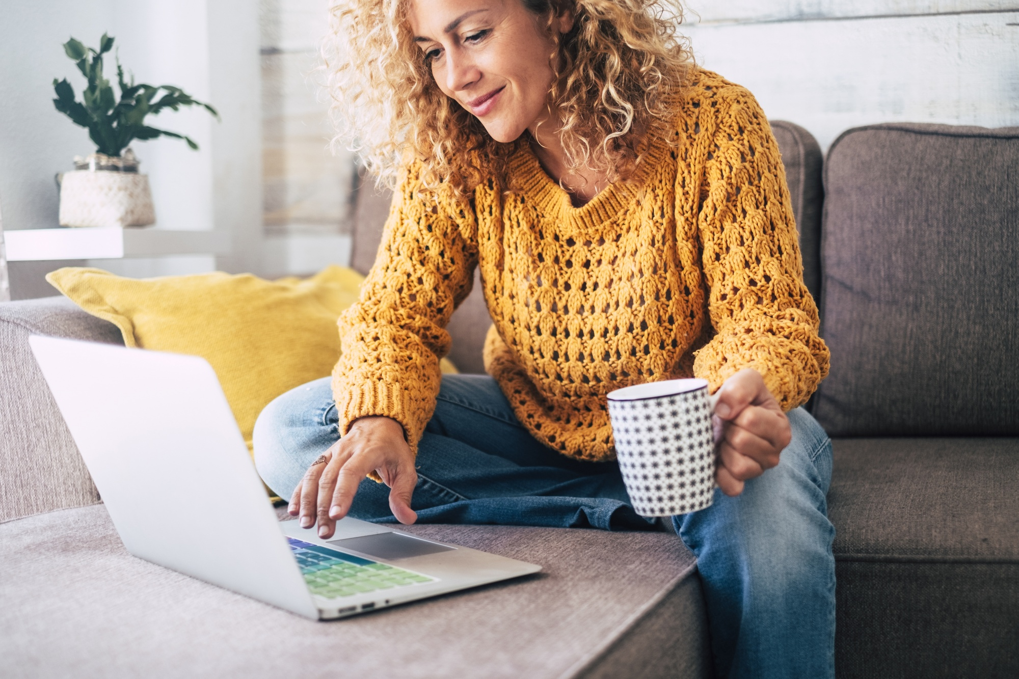 dating profile after 40, woman on sofa relaxing with coffee and typing on computer