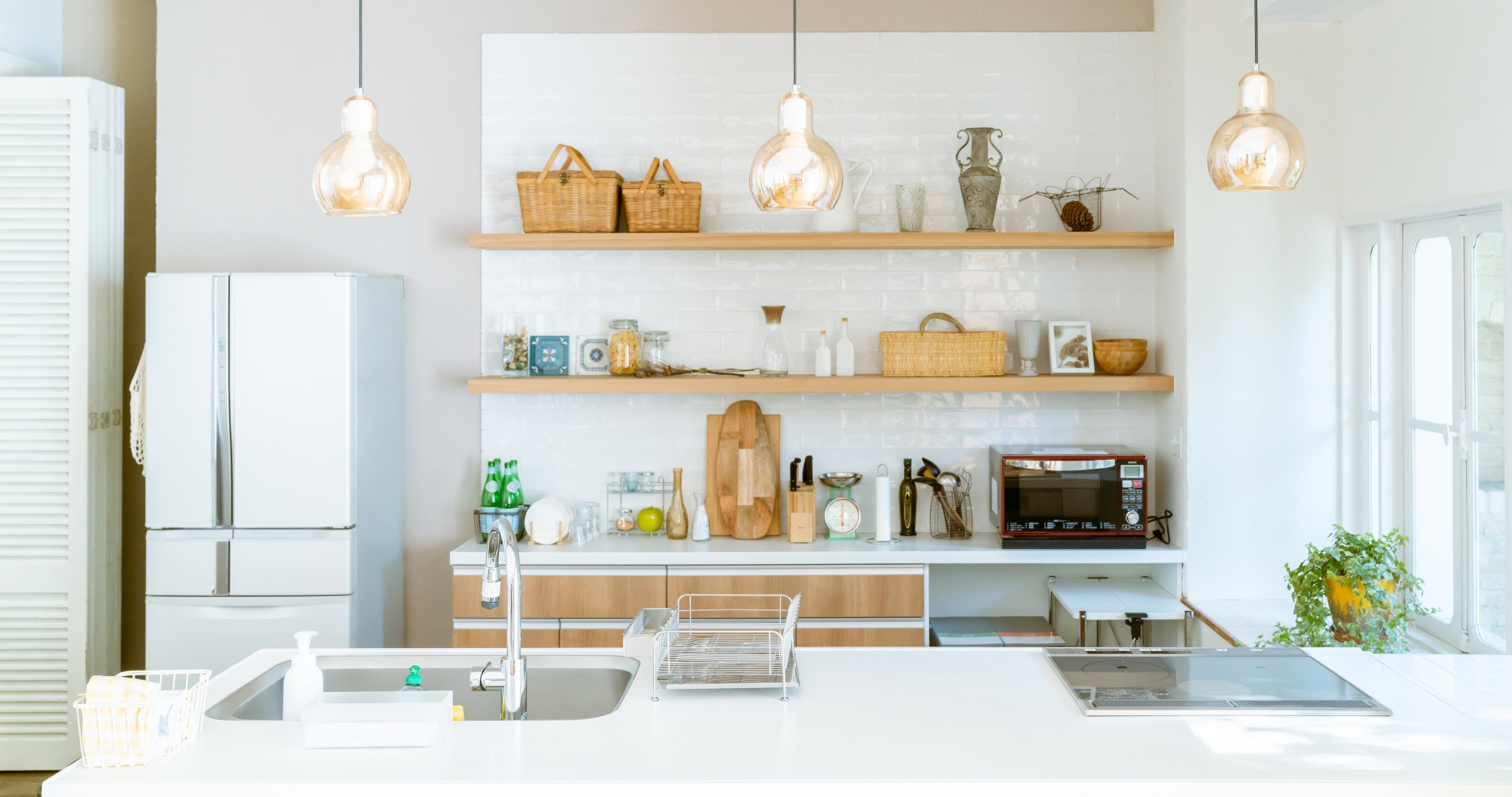 How To Style Pinterest-Worthy Floating Kitchen Shelves row of 3 shelves in kitchen with baskets, canisters, vase