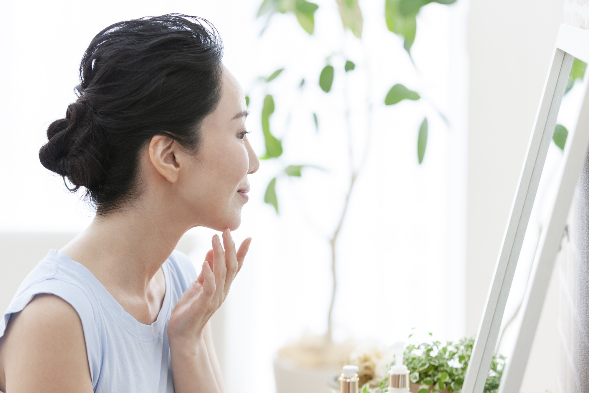 why reinventing yourself makes you younger, Asian woman looking in mirror touching chin