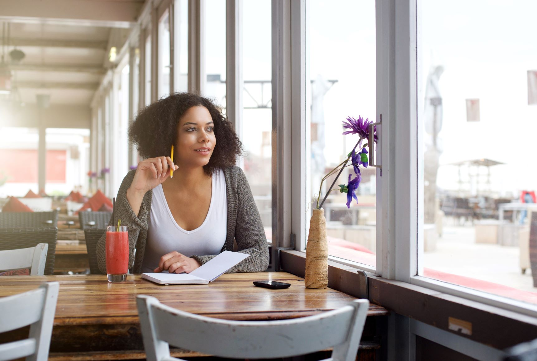 Black woman in white V-neck and grey cardigan at diner table writing and looking out window, manifestation for beginners, manifest your dream life