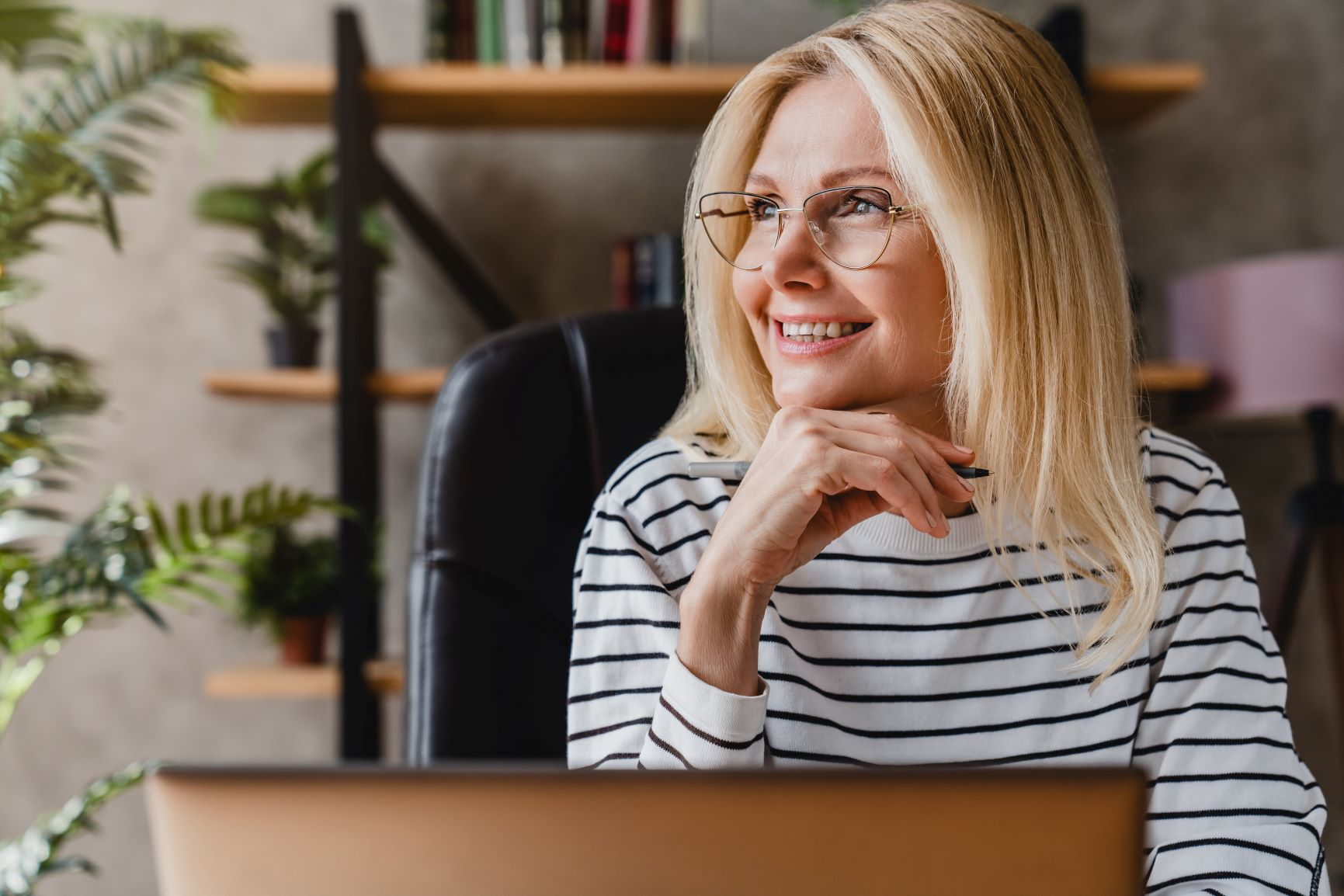 Blonde woman with shoulder-length hair and glasses in white & black striped shirt at comptuer dreaming manifestation for beginners, manifesting your dream life