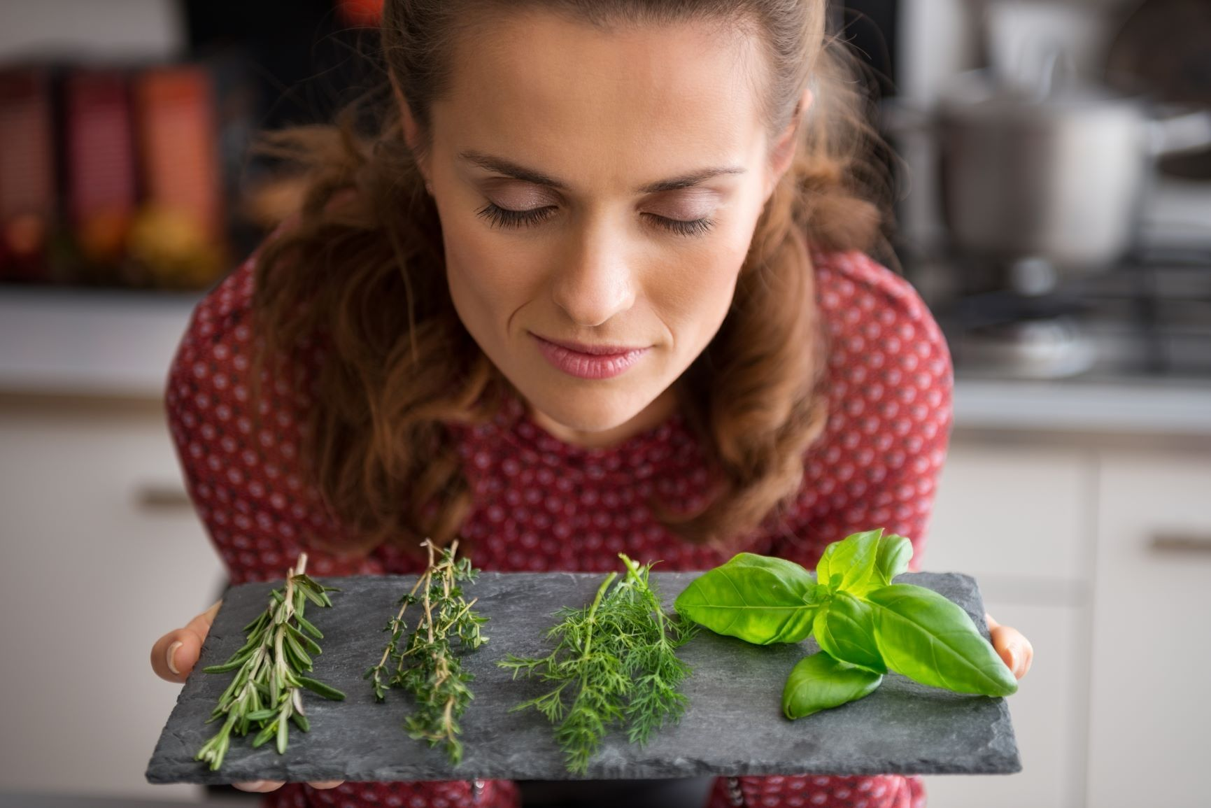 Supercharge your metabolism Brown haired woman in red polk dot blouse leaning over slate cutting board with herbs
