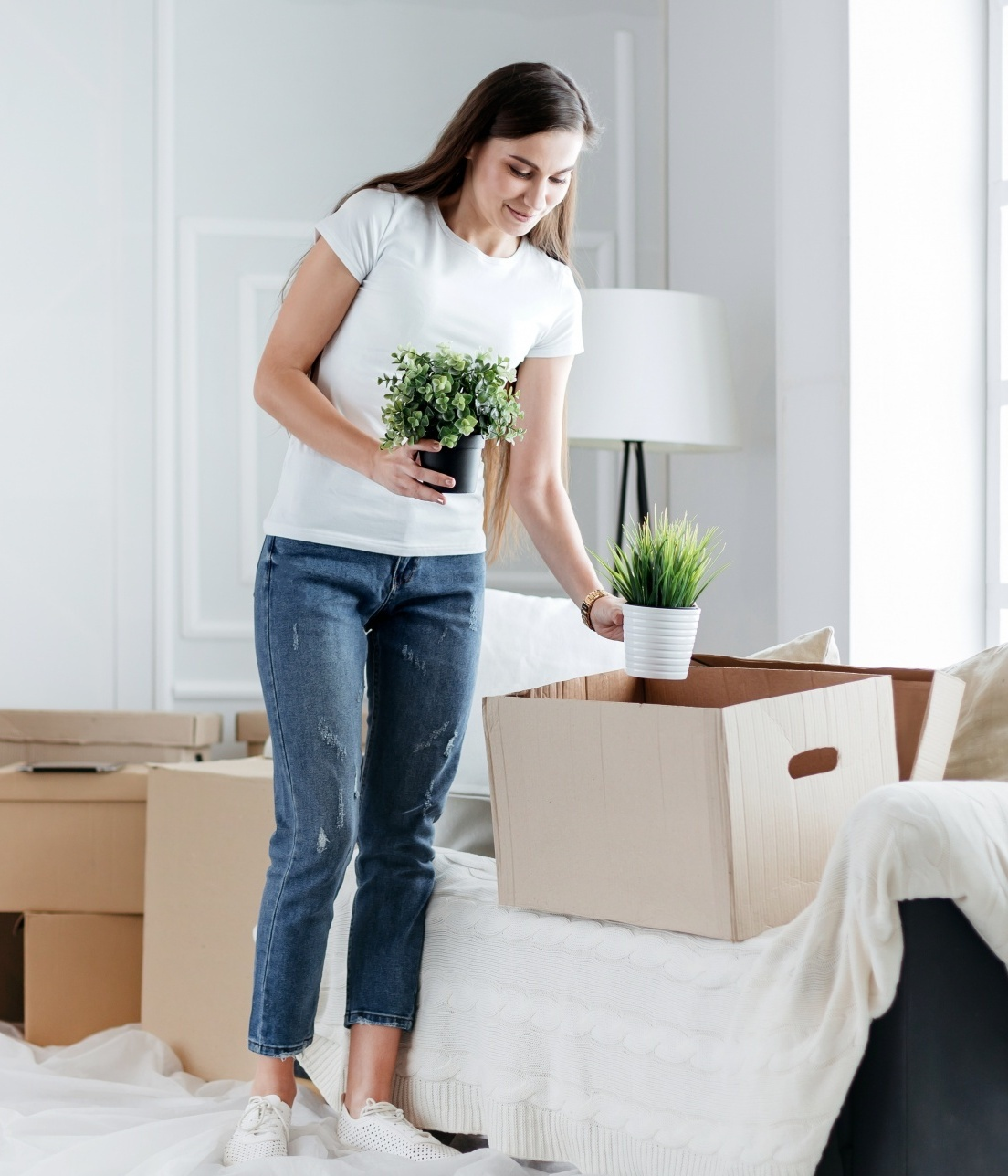 why reinventing yourself makes you younger, Dark haired woman in cropped jeans and white tee unpacking boxesDark haired woman in cropped jeans and white tee unpacking boxes
