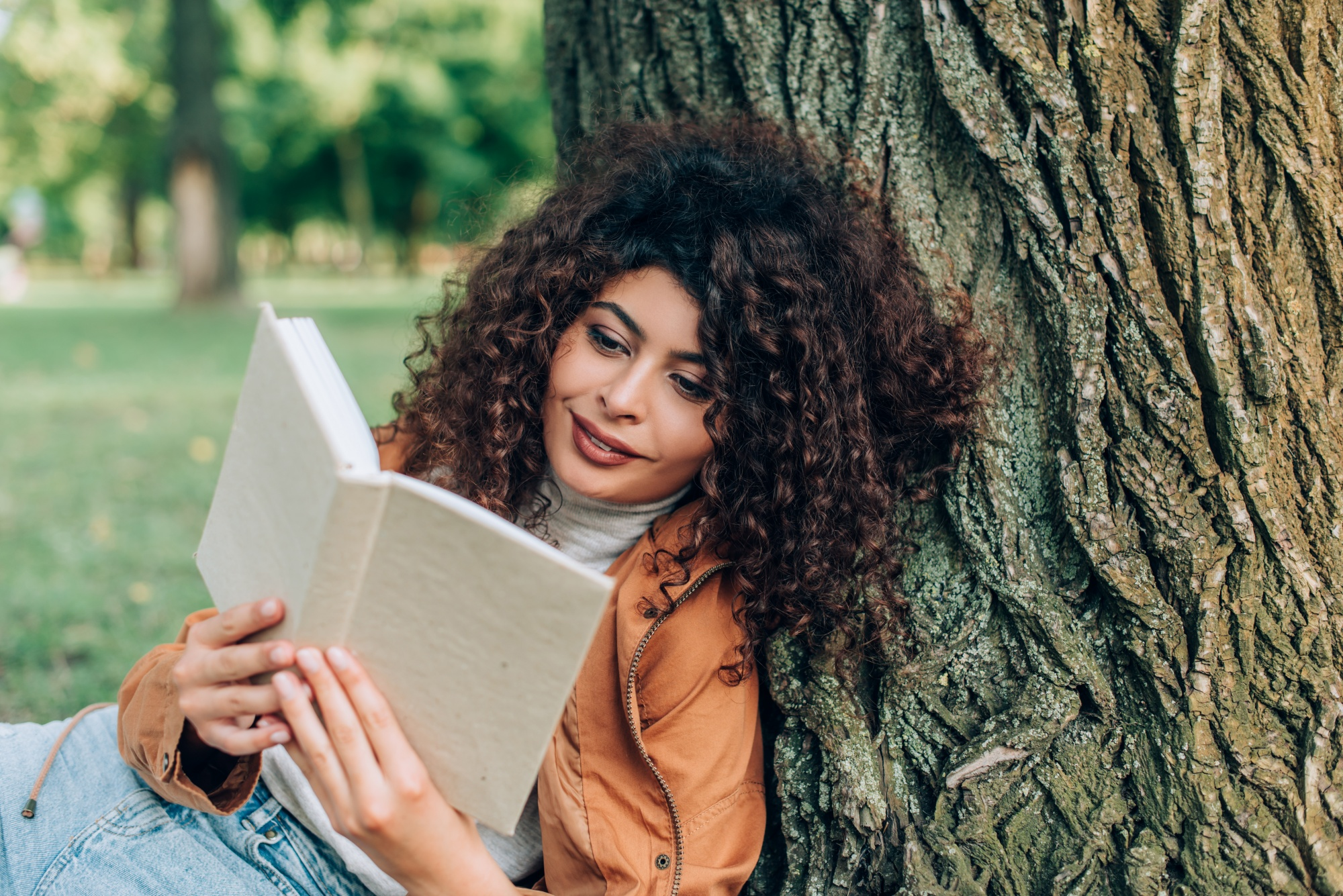 why reinventing yourself makes you younger, Curly woman reading book near tree in park
