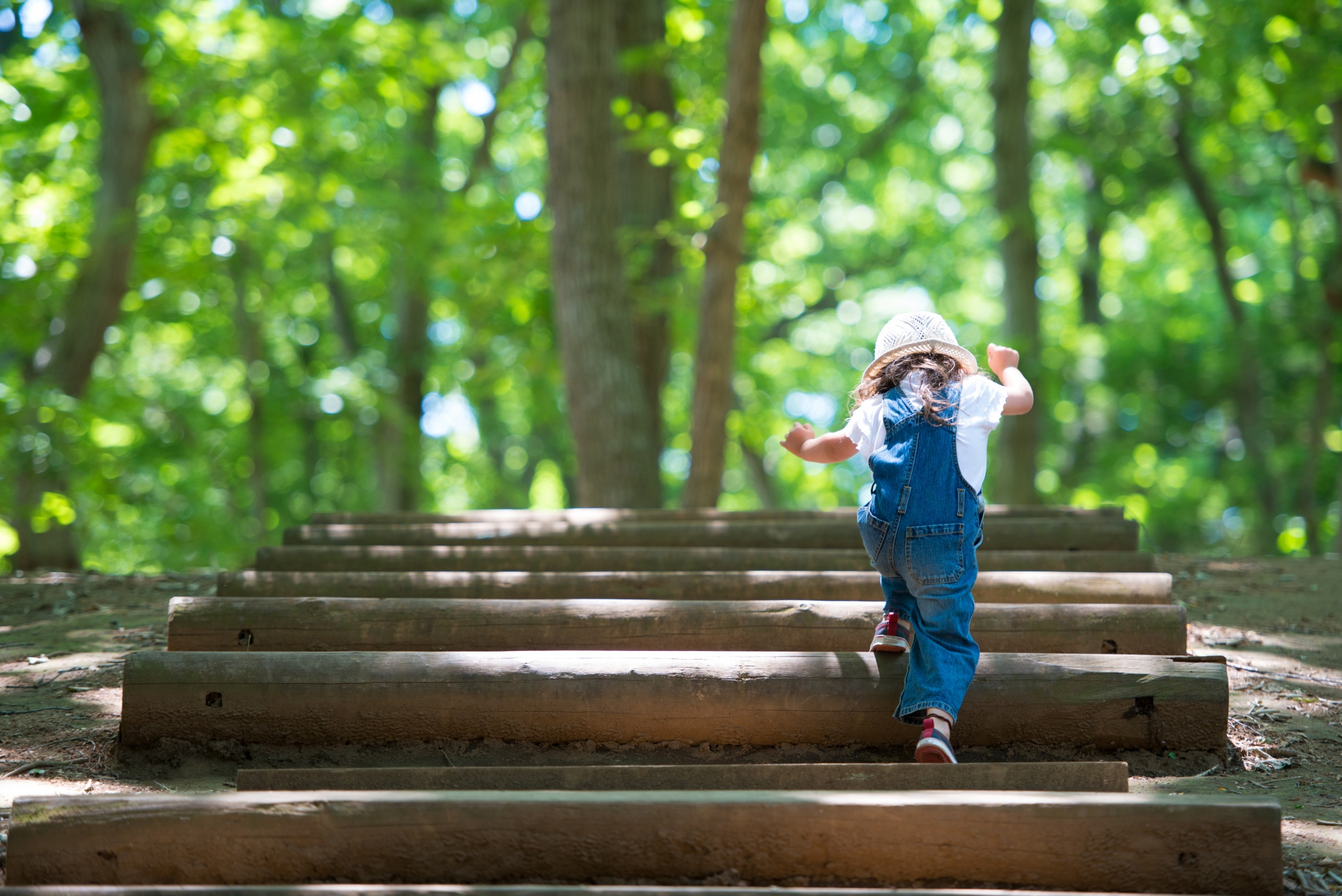 why reinventing yourself makes you younger, Little Girl in denim overalls and pink hat climbing steps in the woods