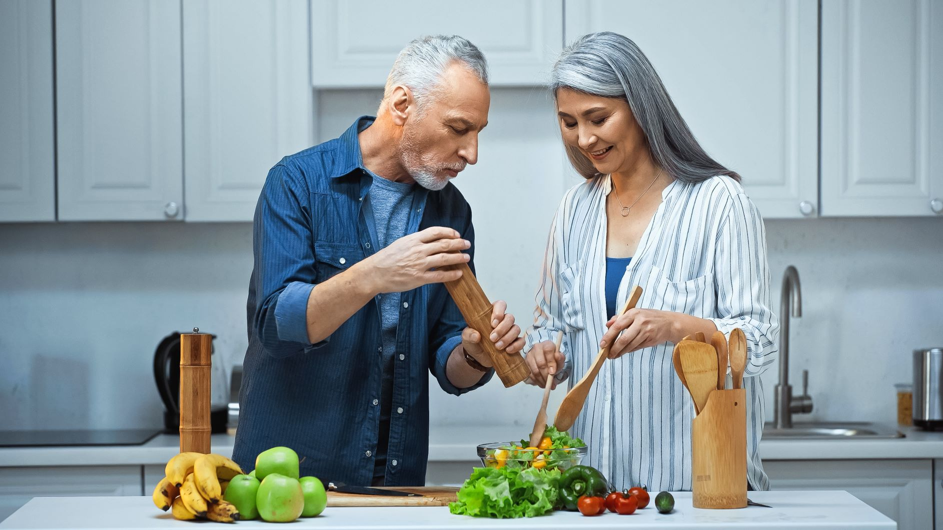 Middle-aged couple adding pepper to salad, best spices for metabolism