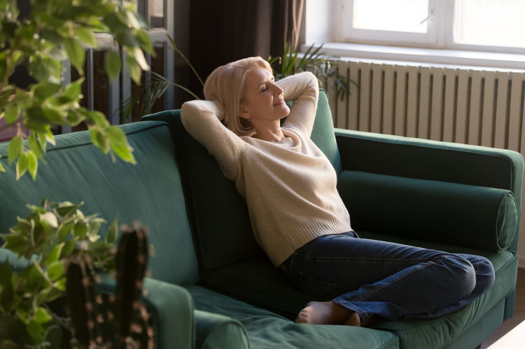 Petite Blond in pink sweater and jeans dreaming on jade couch with plants, manifest your dream life, manifestation for beginners