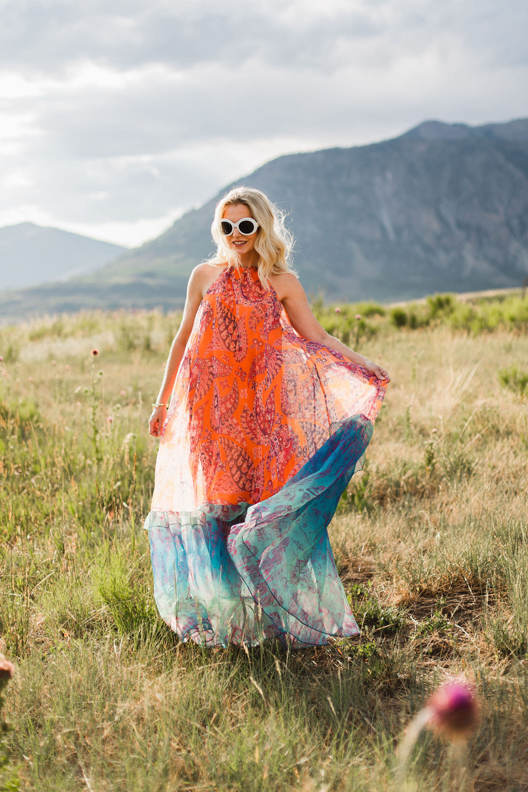 Ina dress by Staud in a tall grass field in the mountains of telluride featuring INA staud dress in orange and blue on fashion over 40 blogger Erin Busbee of Busbee Style