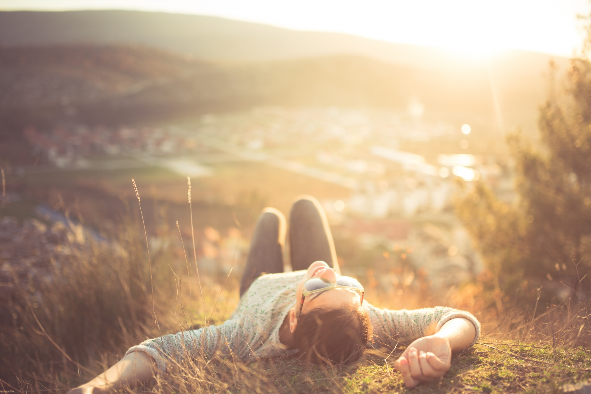 Woman laying on grass on hill above a town manifestation for beginners, manifesting your dream life