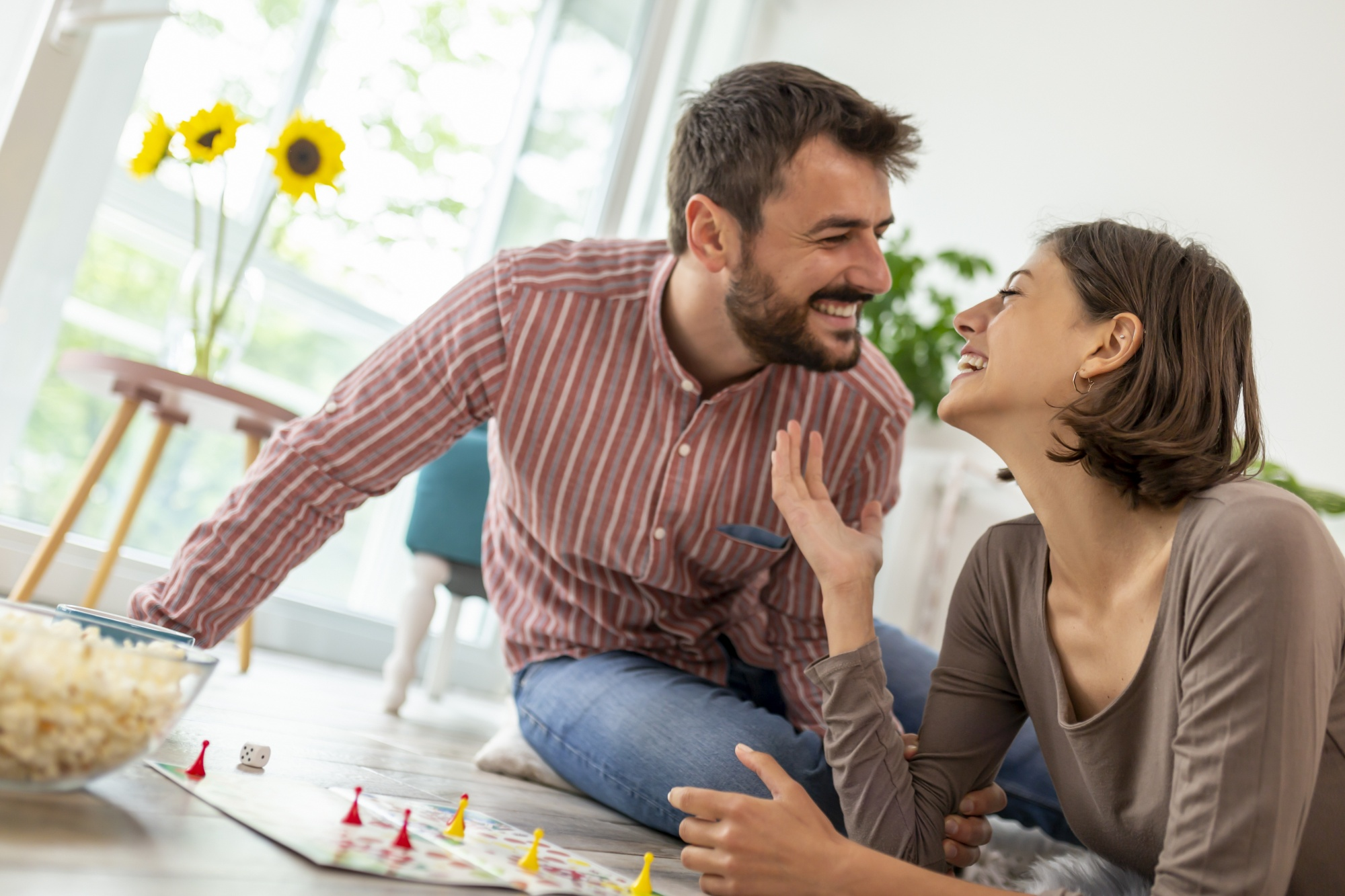 board games for date night, couple laughing having fun playing board game