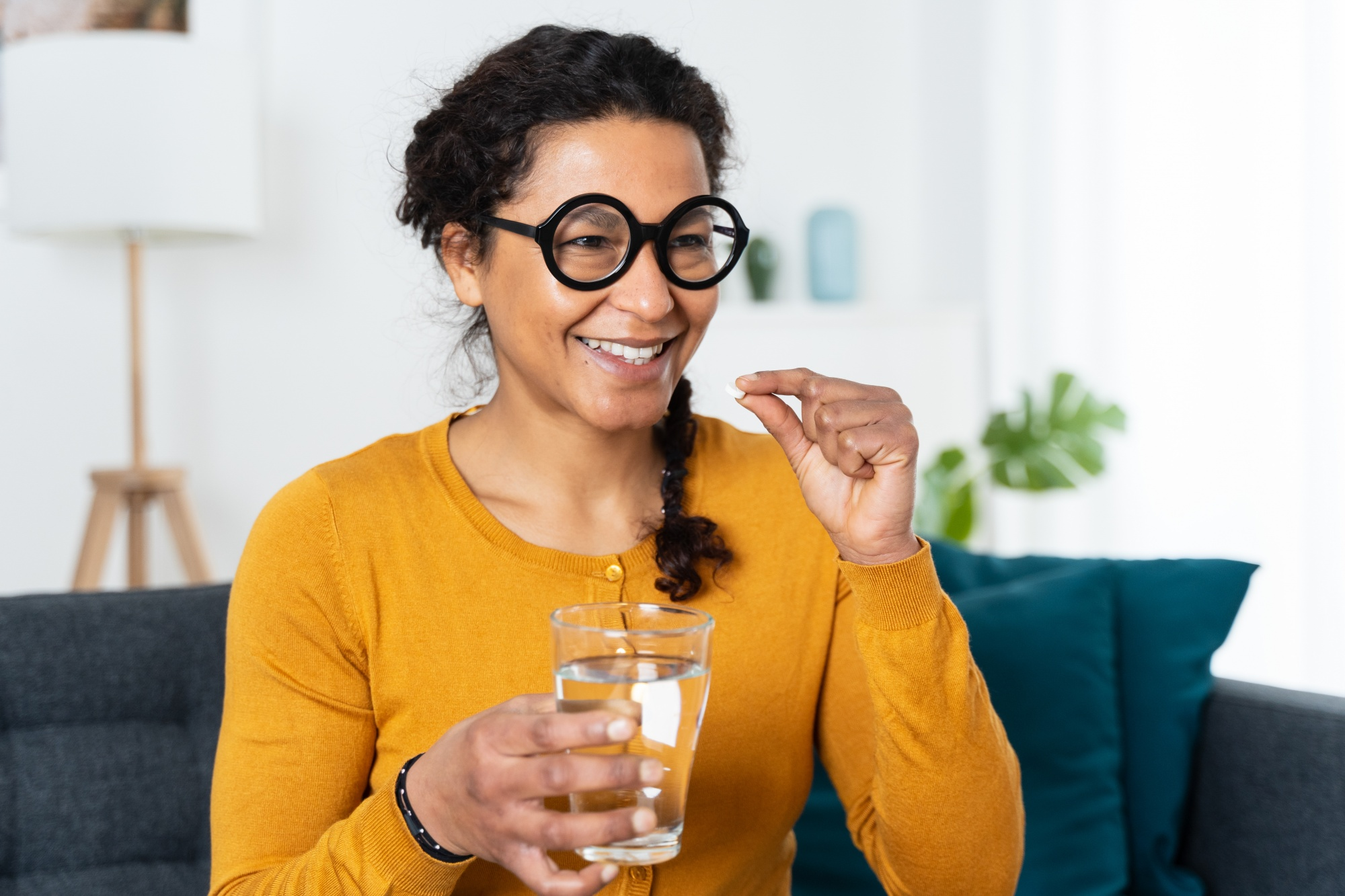 Going Through Menopause? You Should Try Vitamin K2, African American woman holding medicine pills in hand
