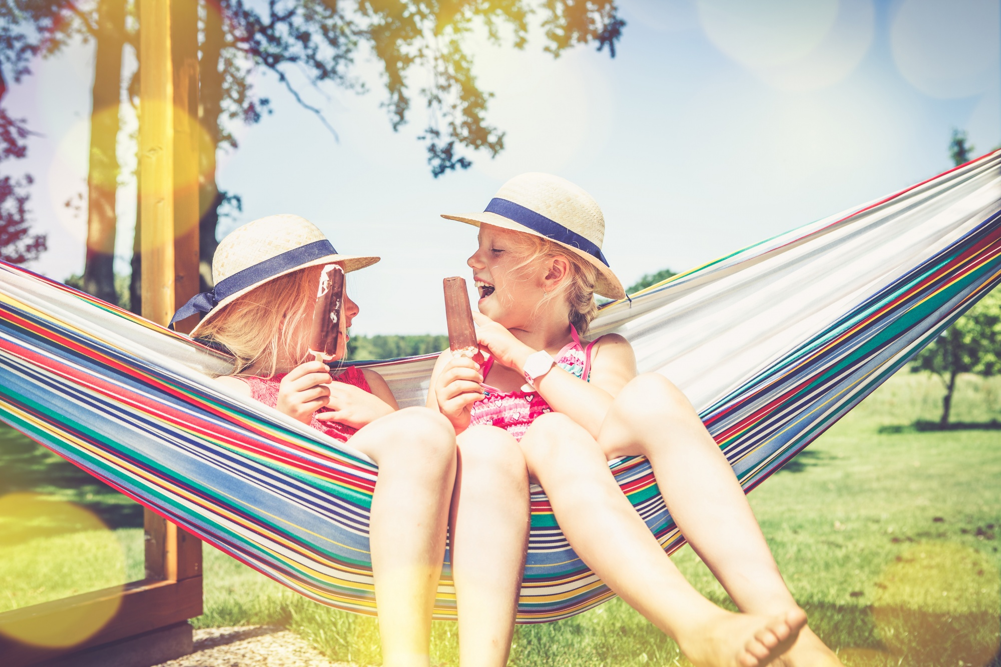 Essentials to Get Your Kids Outdoors, two young girl friends sitting outdoors in a hammock laughing eating ice cream in the summer sun