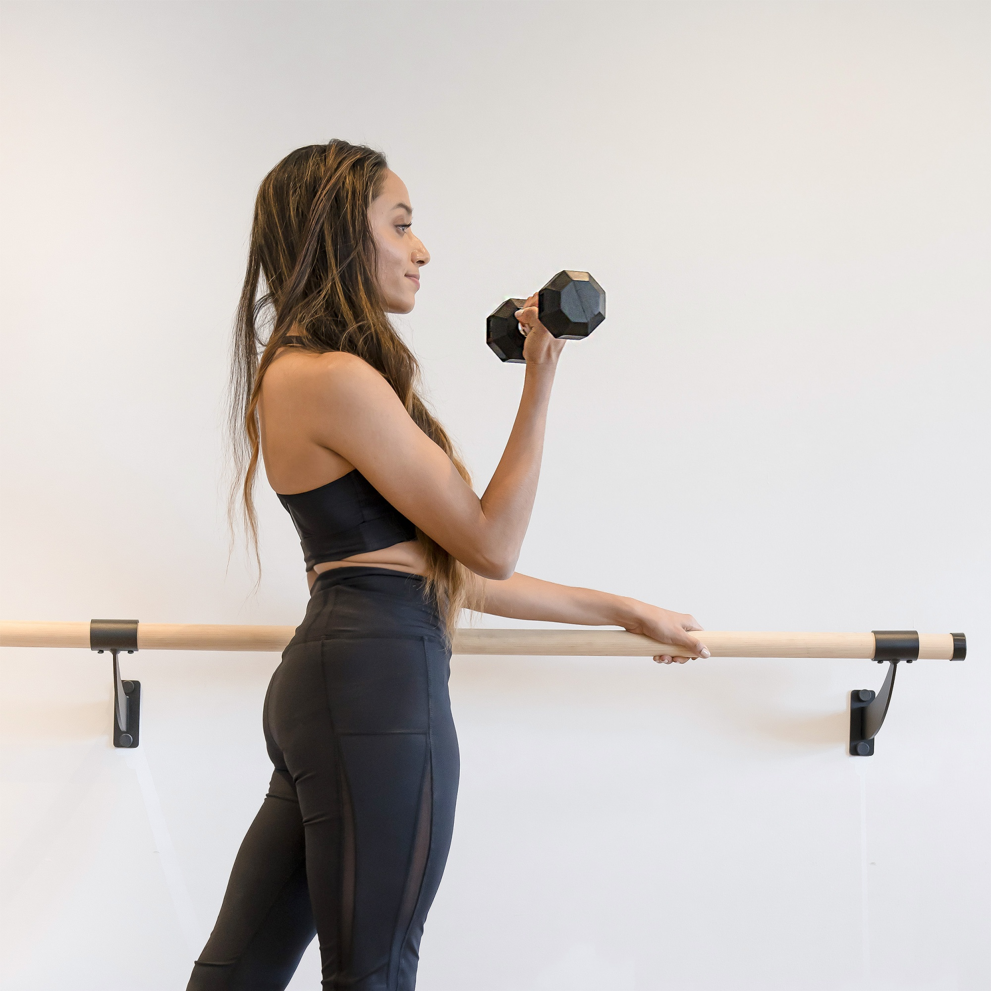 how to get rid of flabby arms, Black woman in black leggings at barre with dumbbell