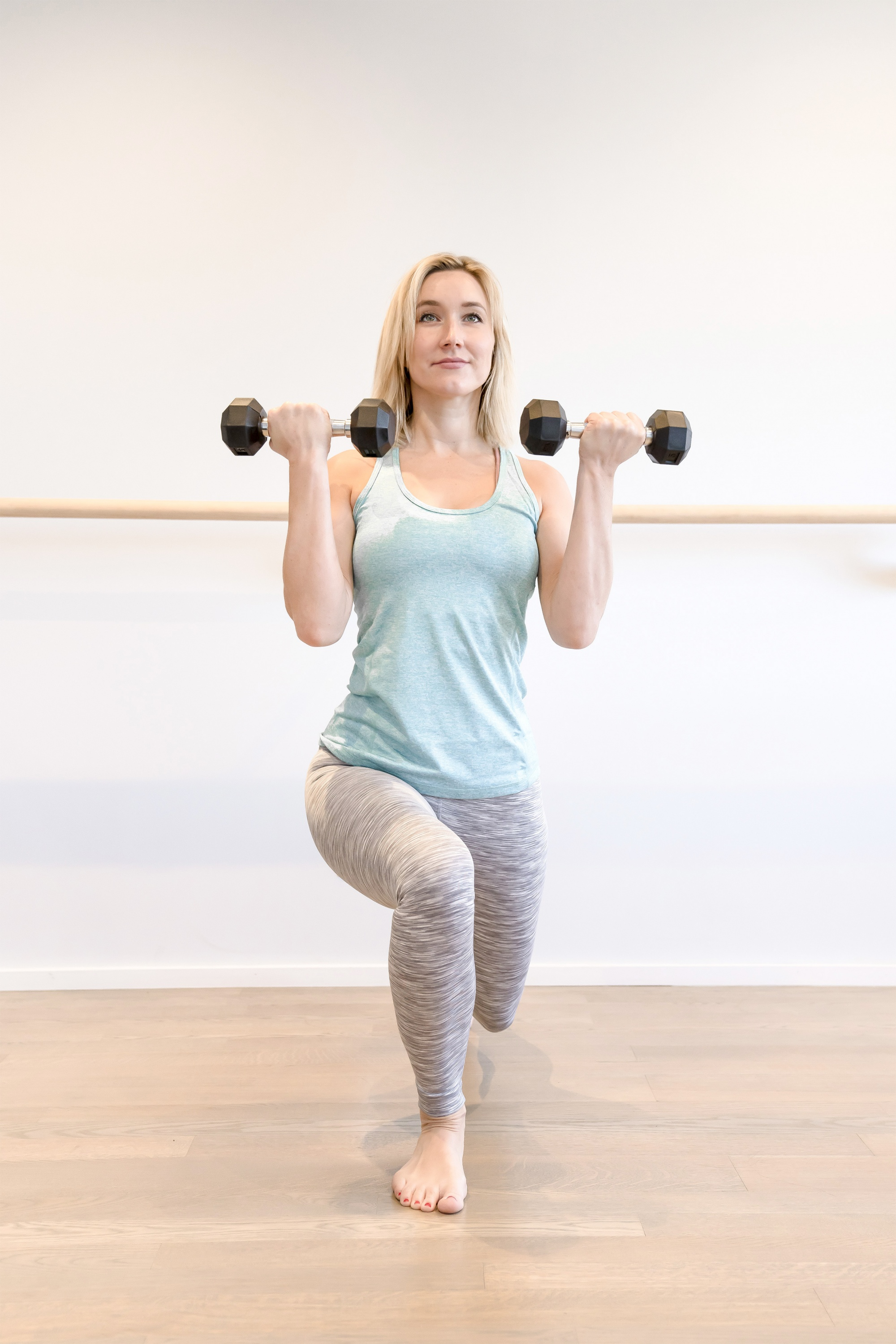 how to get rid of flabby arms, Blonde woman in light blue tank and grey leggings in lunge with dumbbell curl