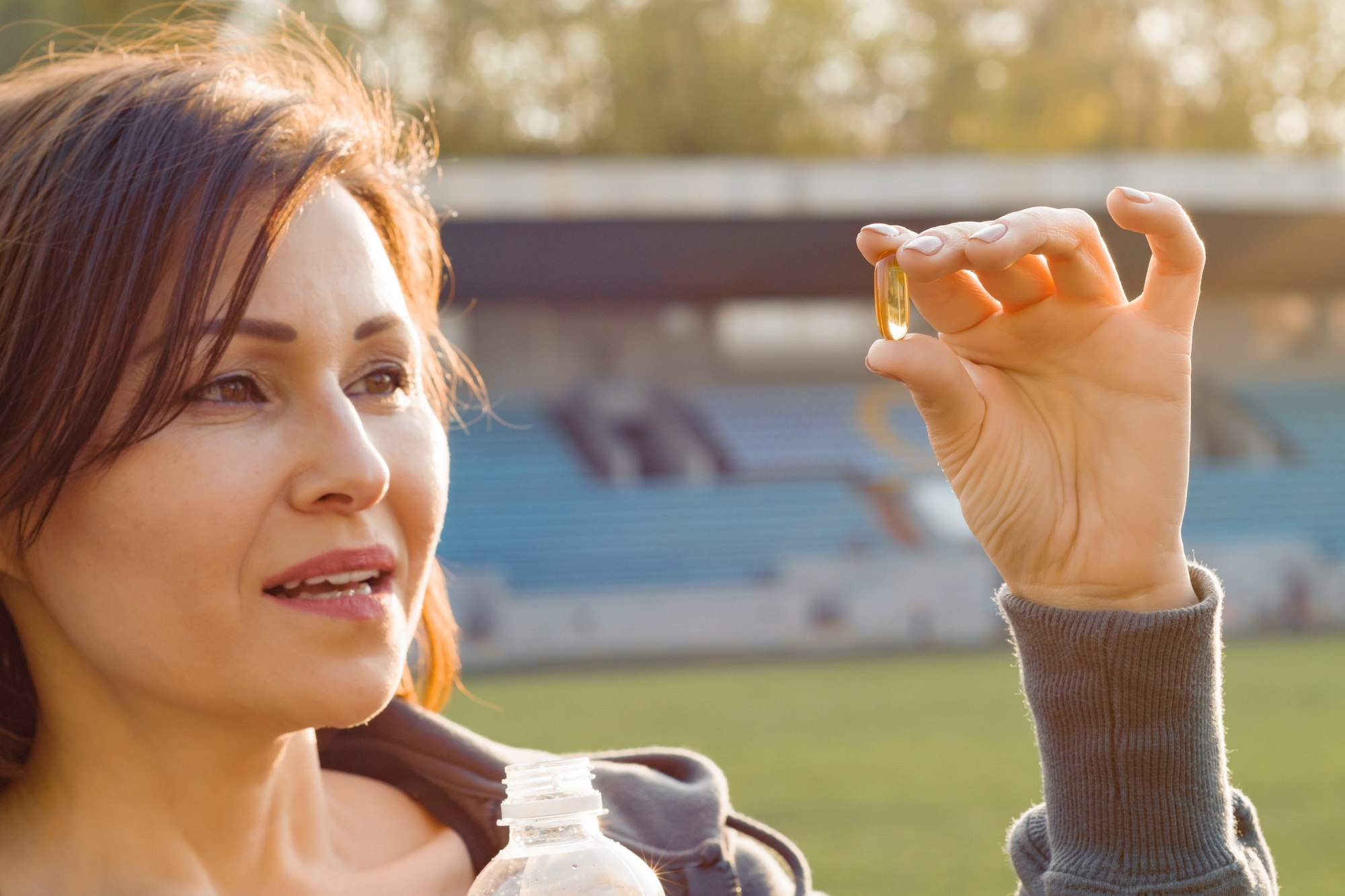 Going Through Menopause? You Should Try Vitamin K2, Dark-haired middle-aged woman taking supplement outside