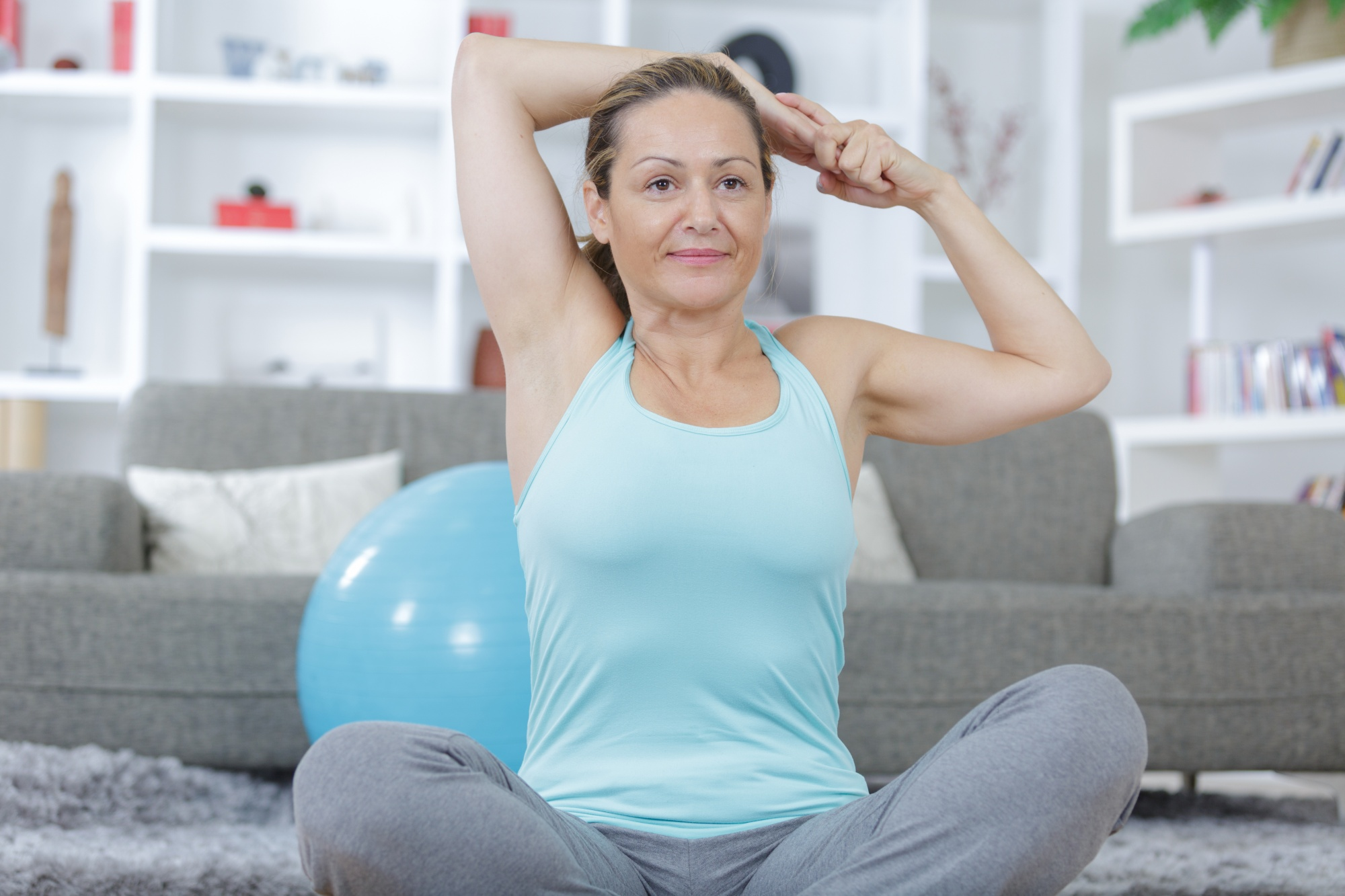 Middle-aged woman in blue tank stretching in her living room, workouts to get your booty swimsuit ready