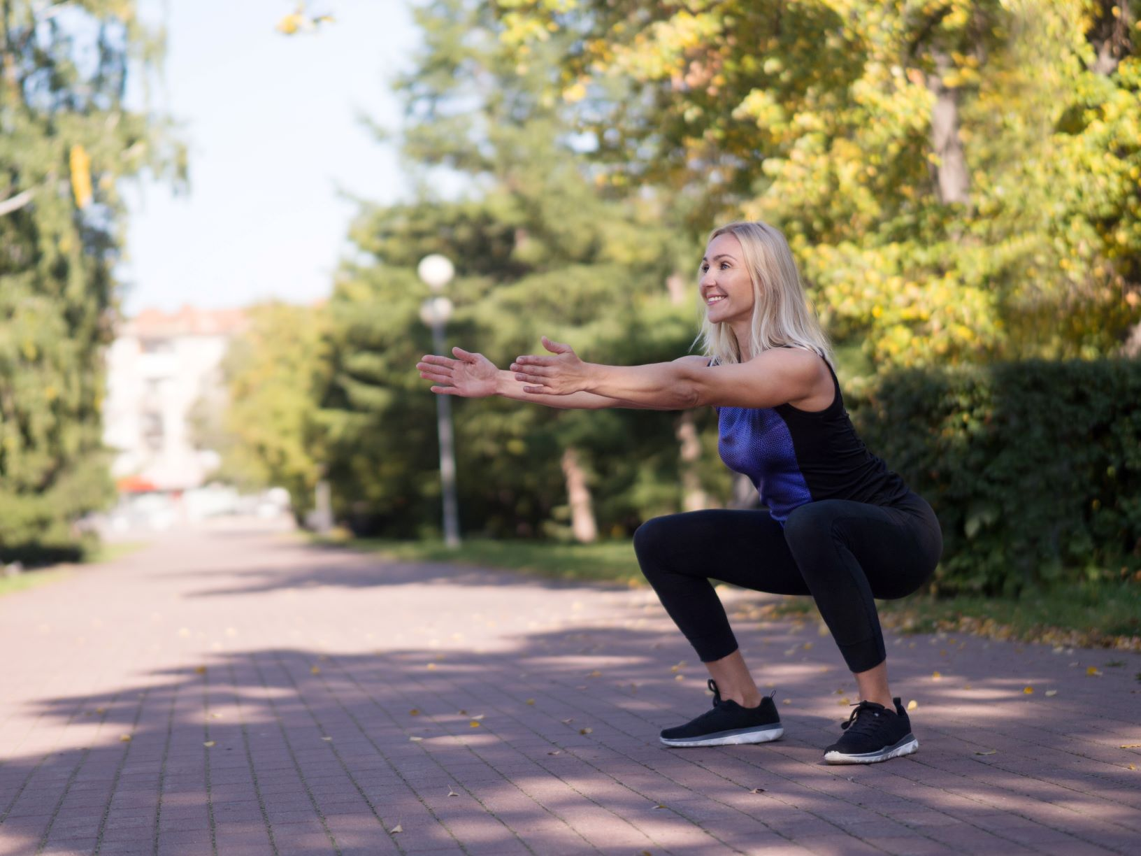 Middle-aged woman outside in deep squat, workouts to get your booty swimsuit ready