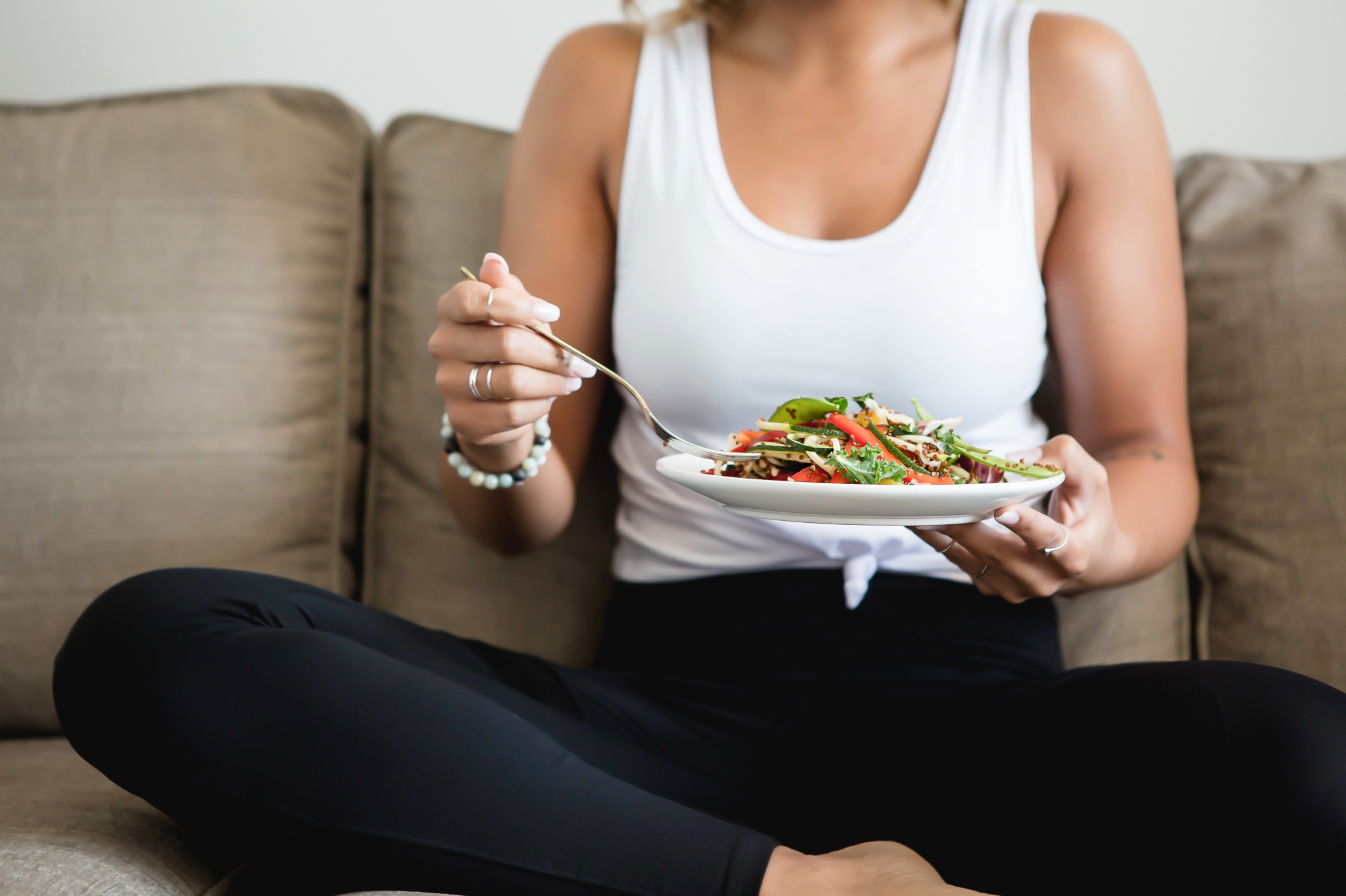 intermittent fasting and intuitive fasting, Woman in white tank and black leggings eating salad on her couch
