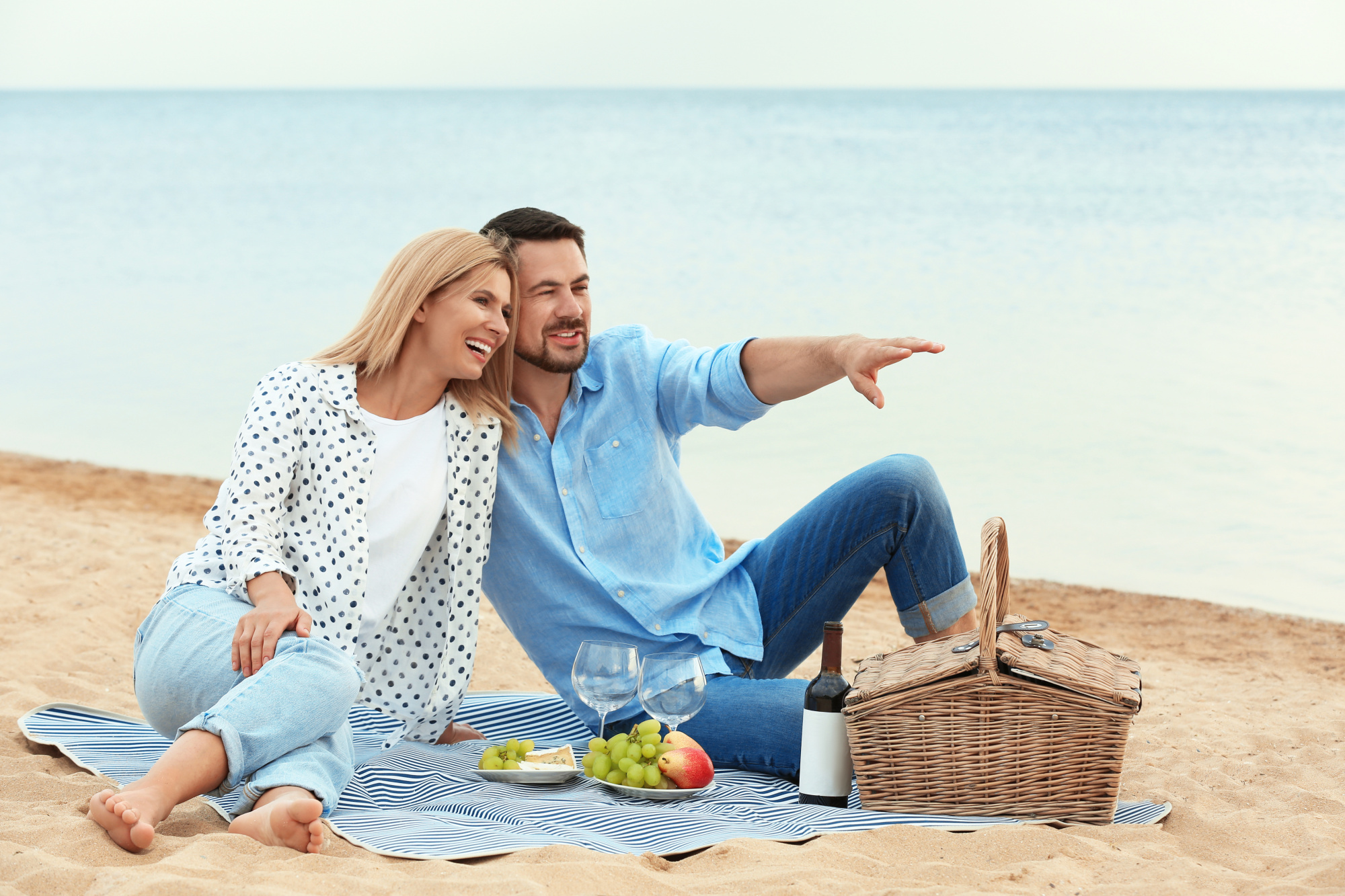 romantic picnic for two, couple sitting on picnic blanket at the beach