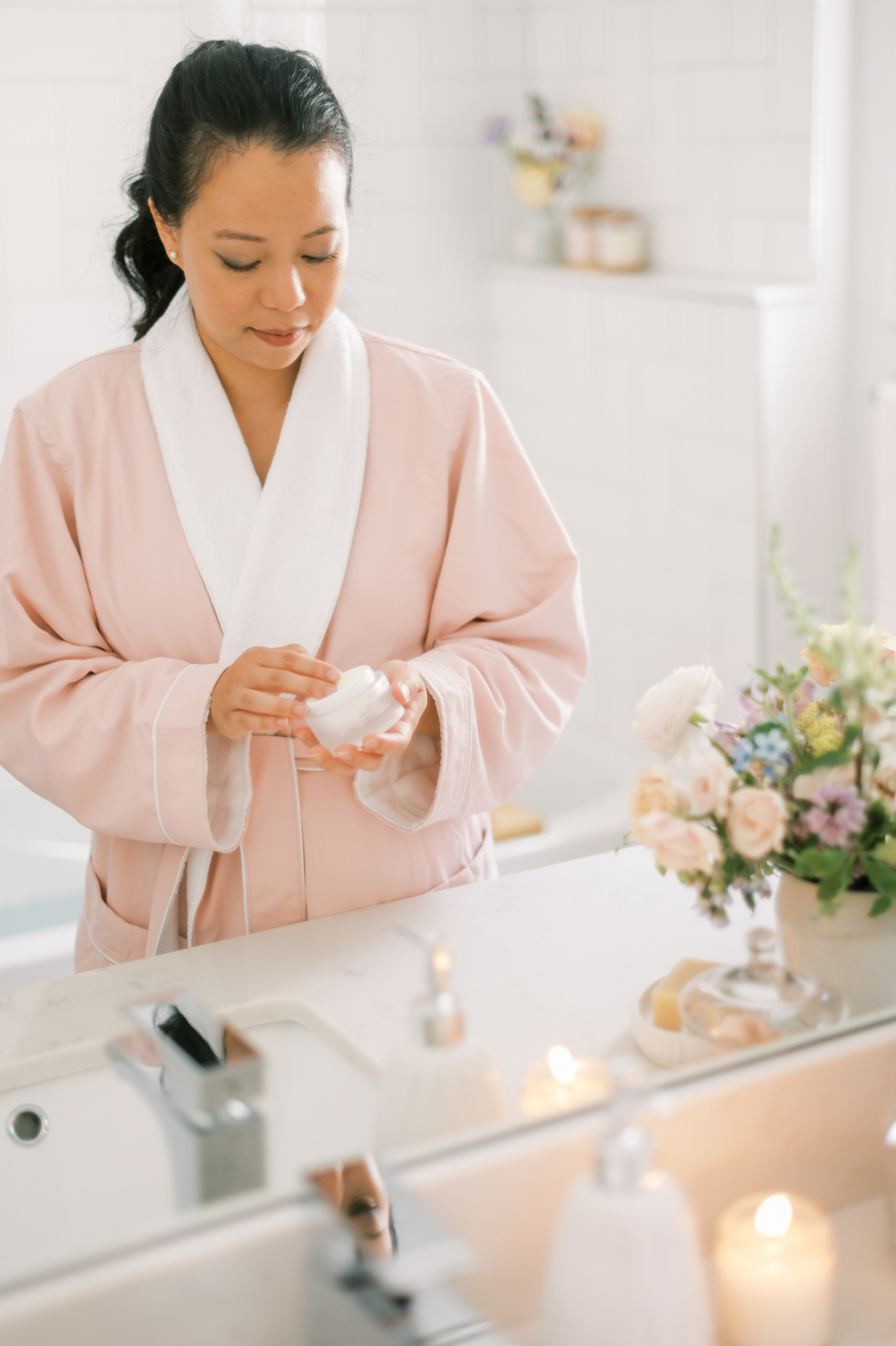 common menopause questions, Asian woman in pink robe applying cream