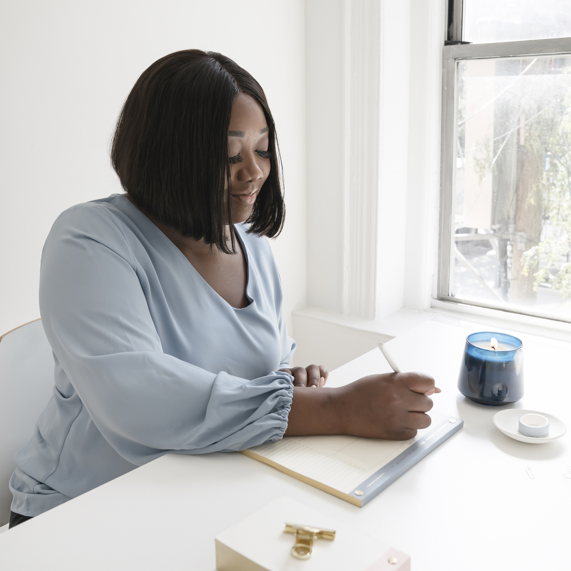 common menopause questions, Black woman with chin-length hair in blue blouse writing
