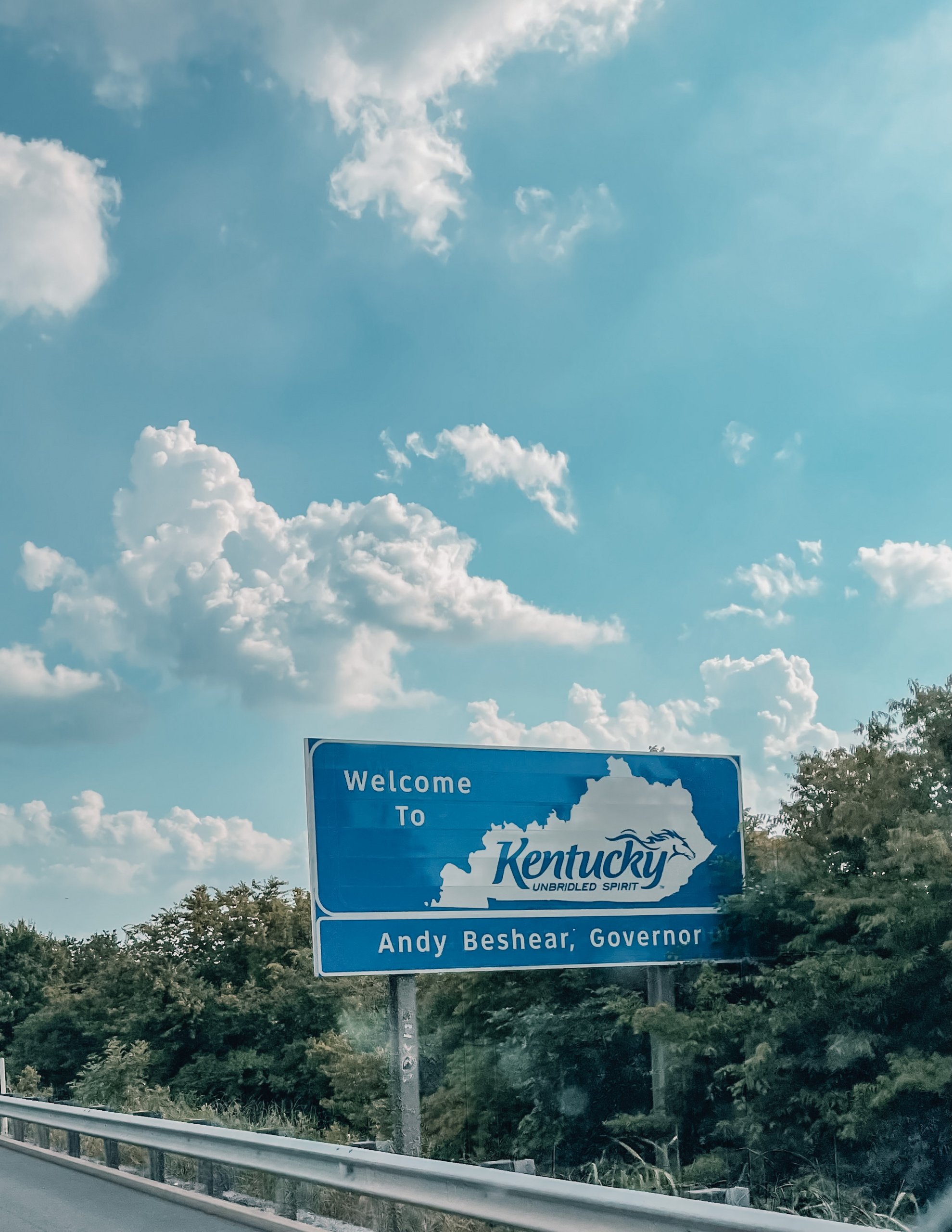 where to stop on a cross-country road trip, best places to stop on a cross country road trip, cross country road trip, west coast to east coast road trip, erin busbee, traveling with kids, how to travel with kids, how to travel with a dog, cross country road trip with kids, kentucky state line welcome sign, cross country busbee style, family road trip