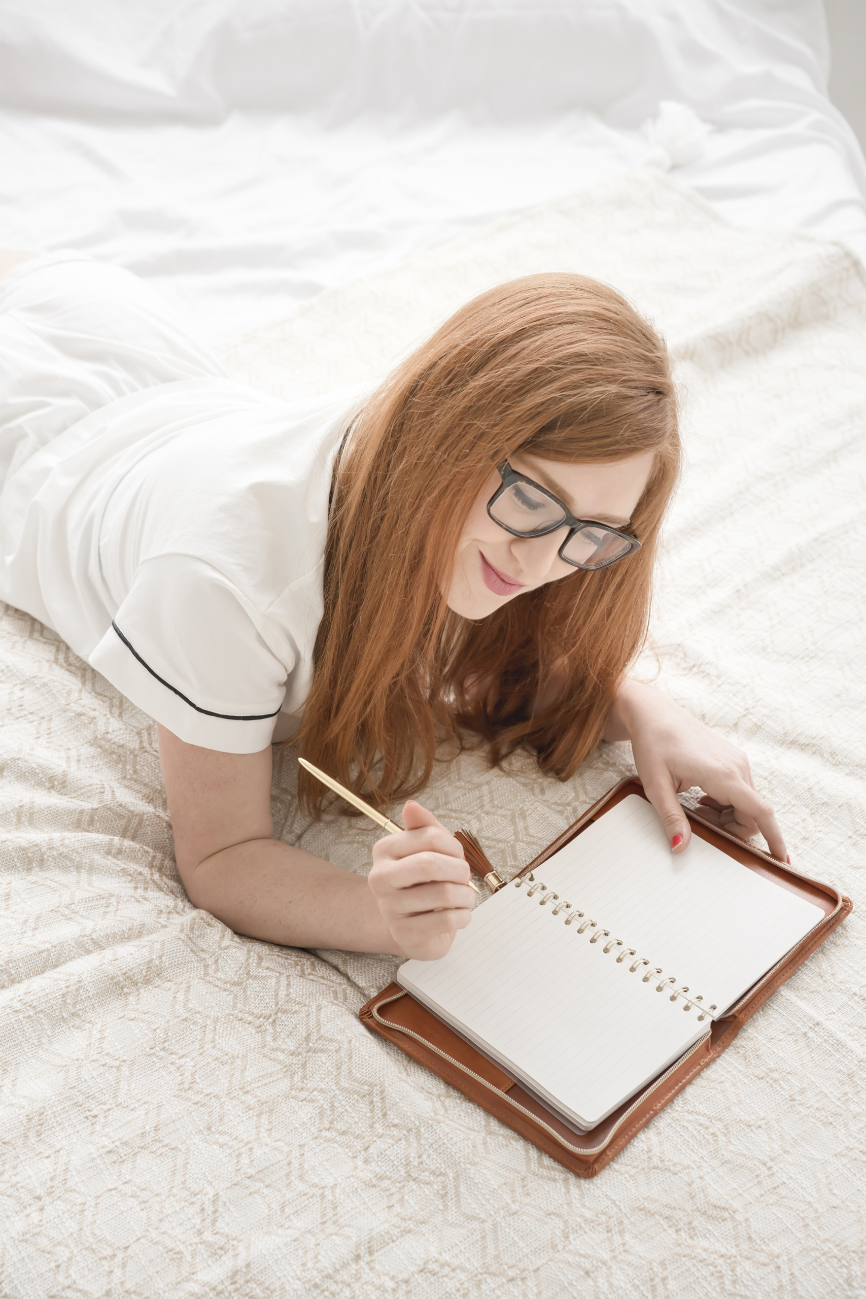 common menopause questions, Long auburn-haired woman journaling in bed
