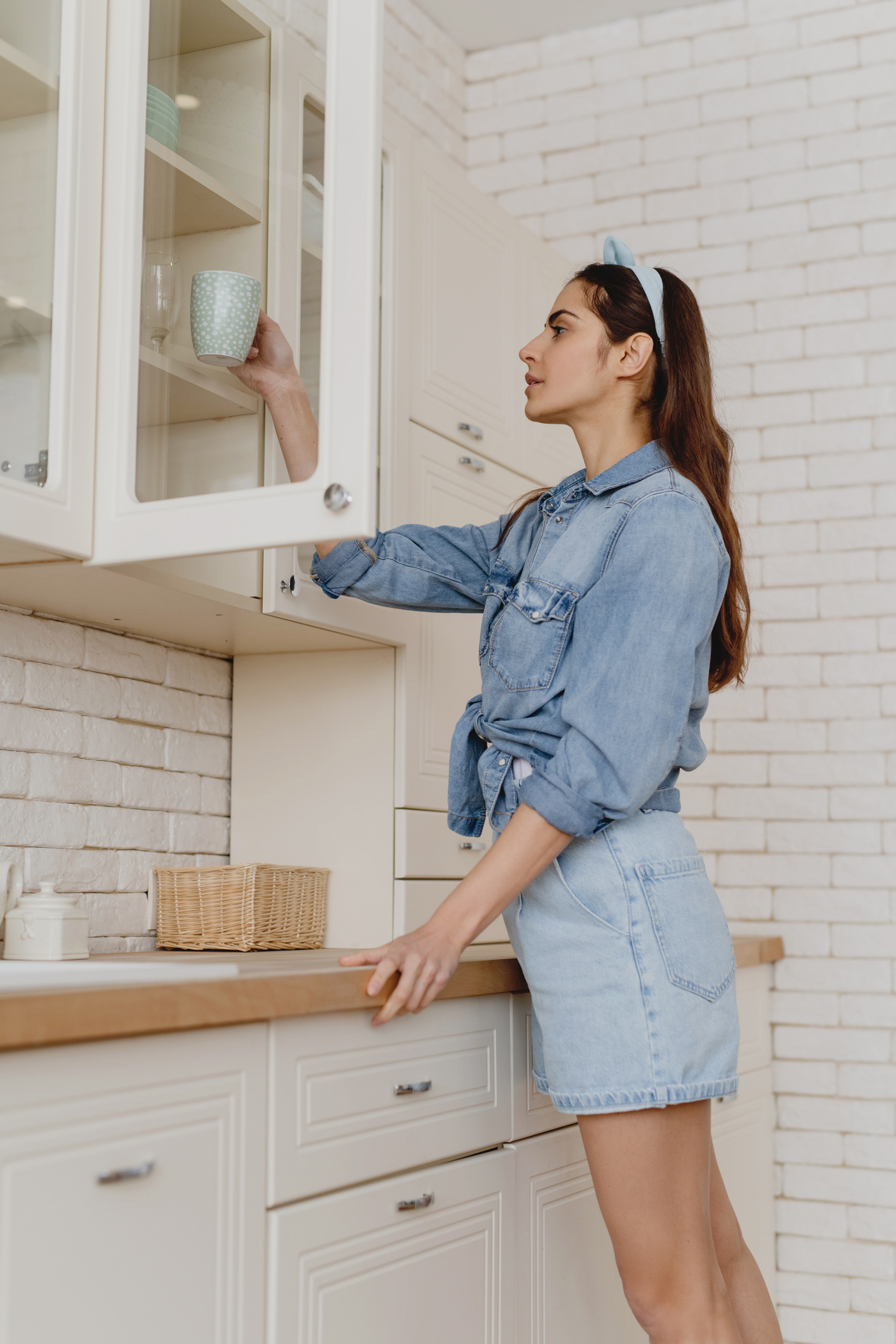 common menopause questions, Long-haired brunette in denim putting mug away in white kitchen