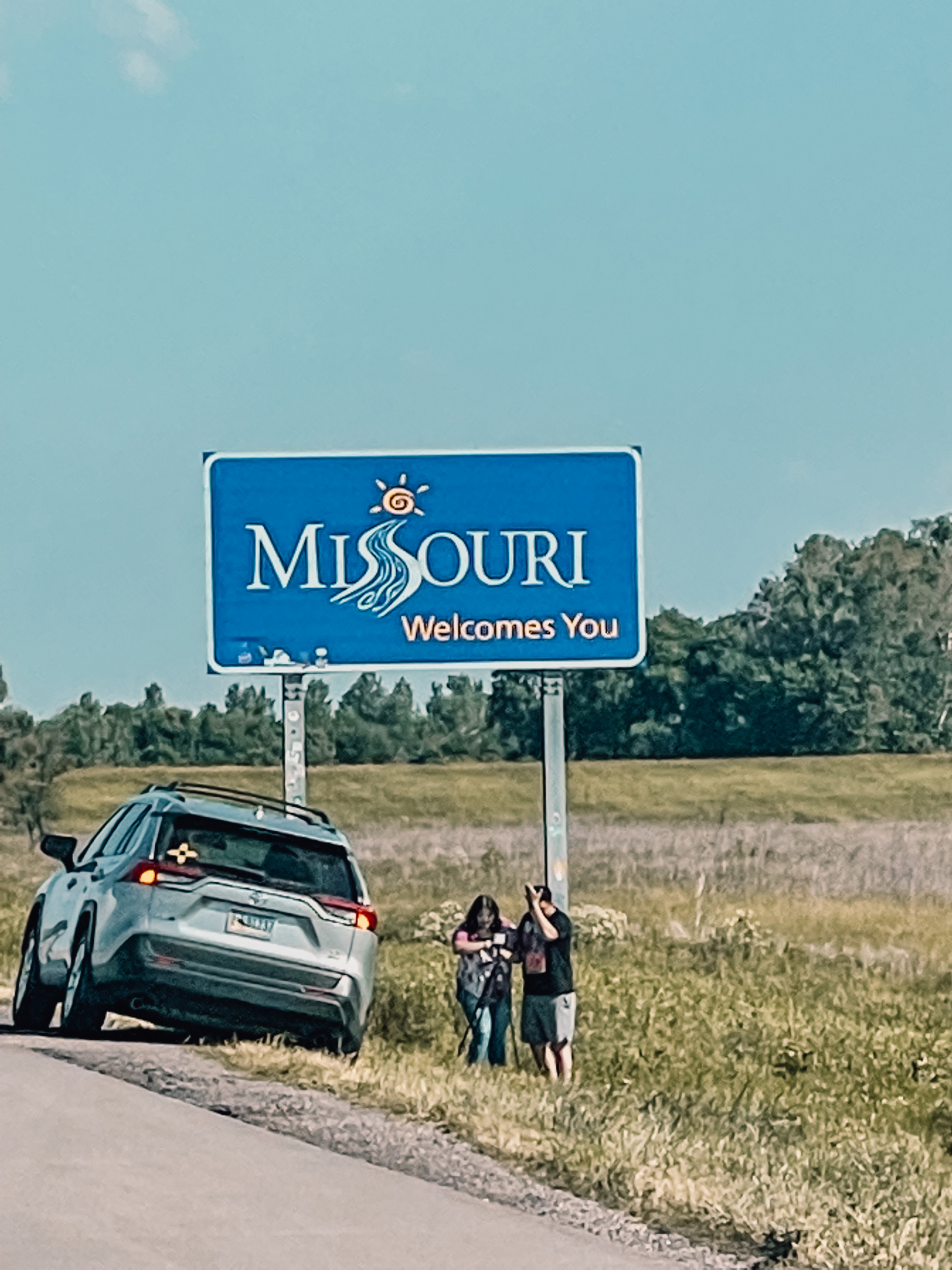 where to stop on a cross-country road trip, best places to stop on a cross country road trip, cross country road trip, west coast to east coast road trip, erin busbee, traveling with kids, how to travel with kids, how to travel with a dog, cross country road trip with kids, missouri state line welcome sign, cross country busbee style, family road trip