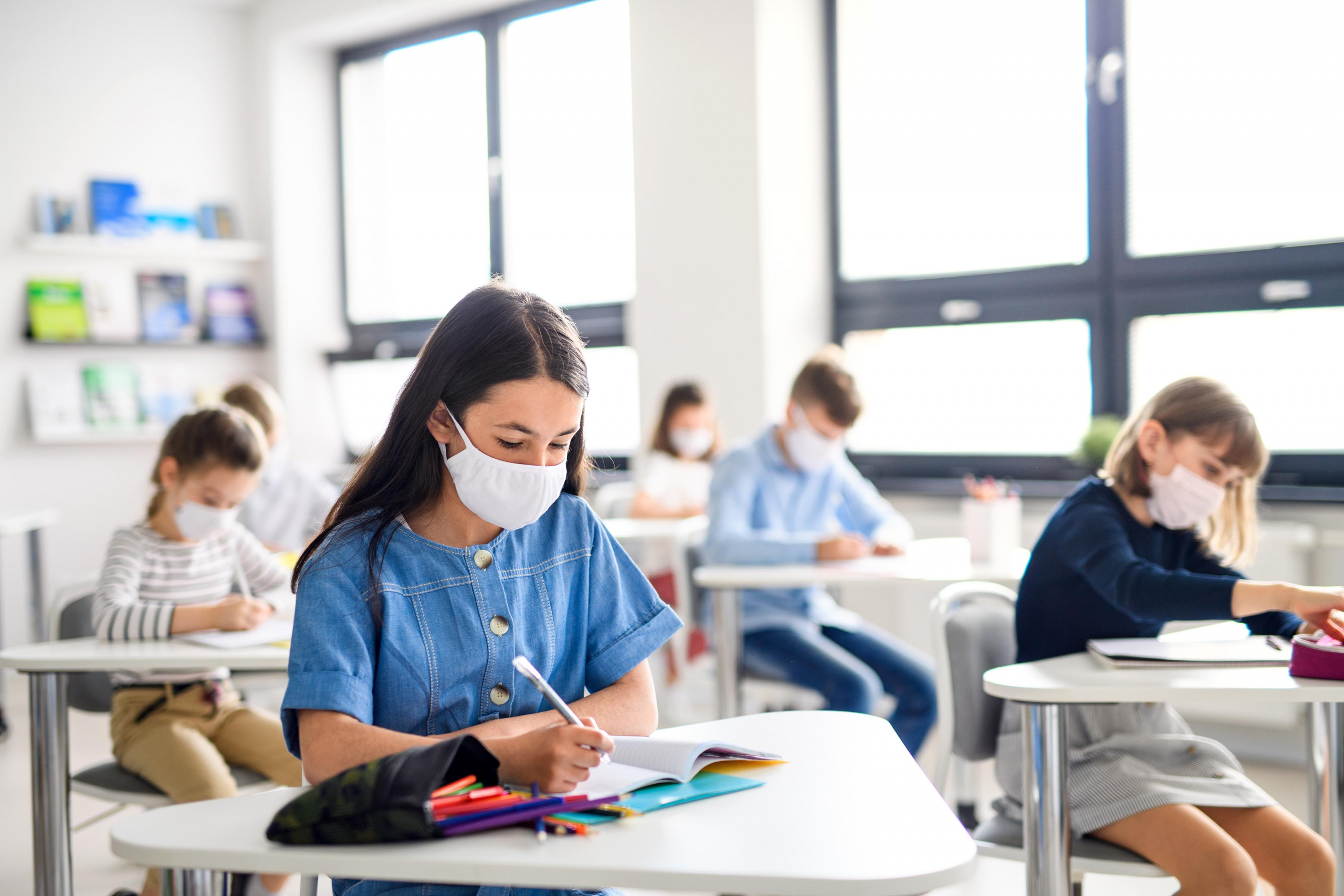 back to school essentials, middle school children students working the classroom wearing masks