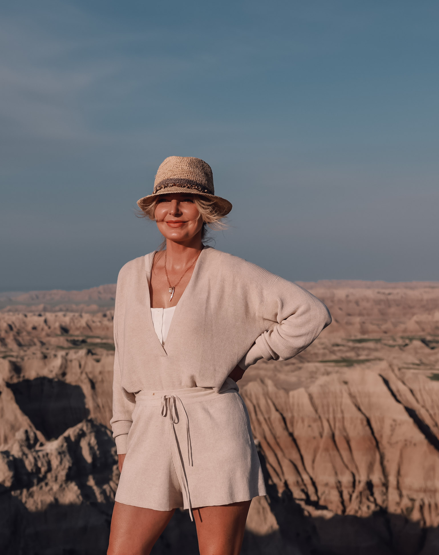 beige knit sweater and shorts set paired with packable straw fedora hat in Badlands National Park on fashion over 40 blogger Erin Busbee